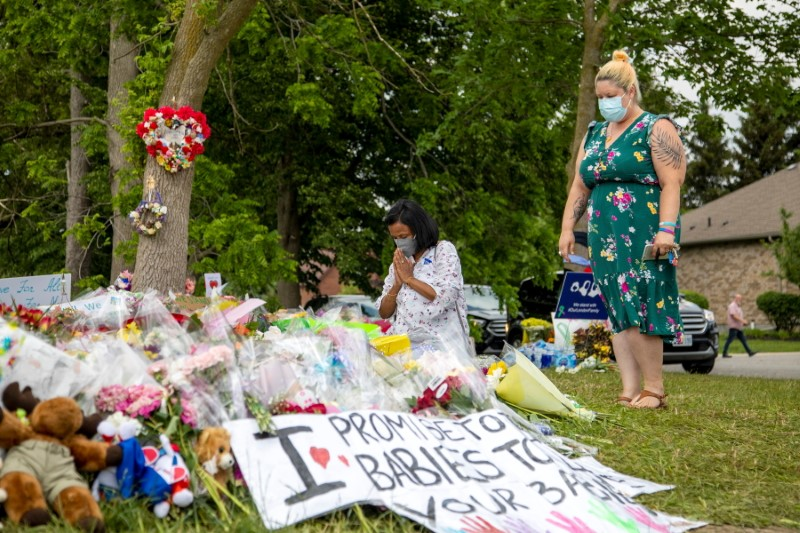 People are seen at a makeshift memorial at the fatal crime scene where a man driving a pickup truck jumped the curb and ran over a Muslim family in what police say was a deliberately targeted anti-Islamic hate crime, in London, Ontario, Canada June 9, 2021. REUTERS/Carlos Osorio