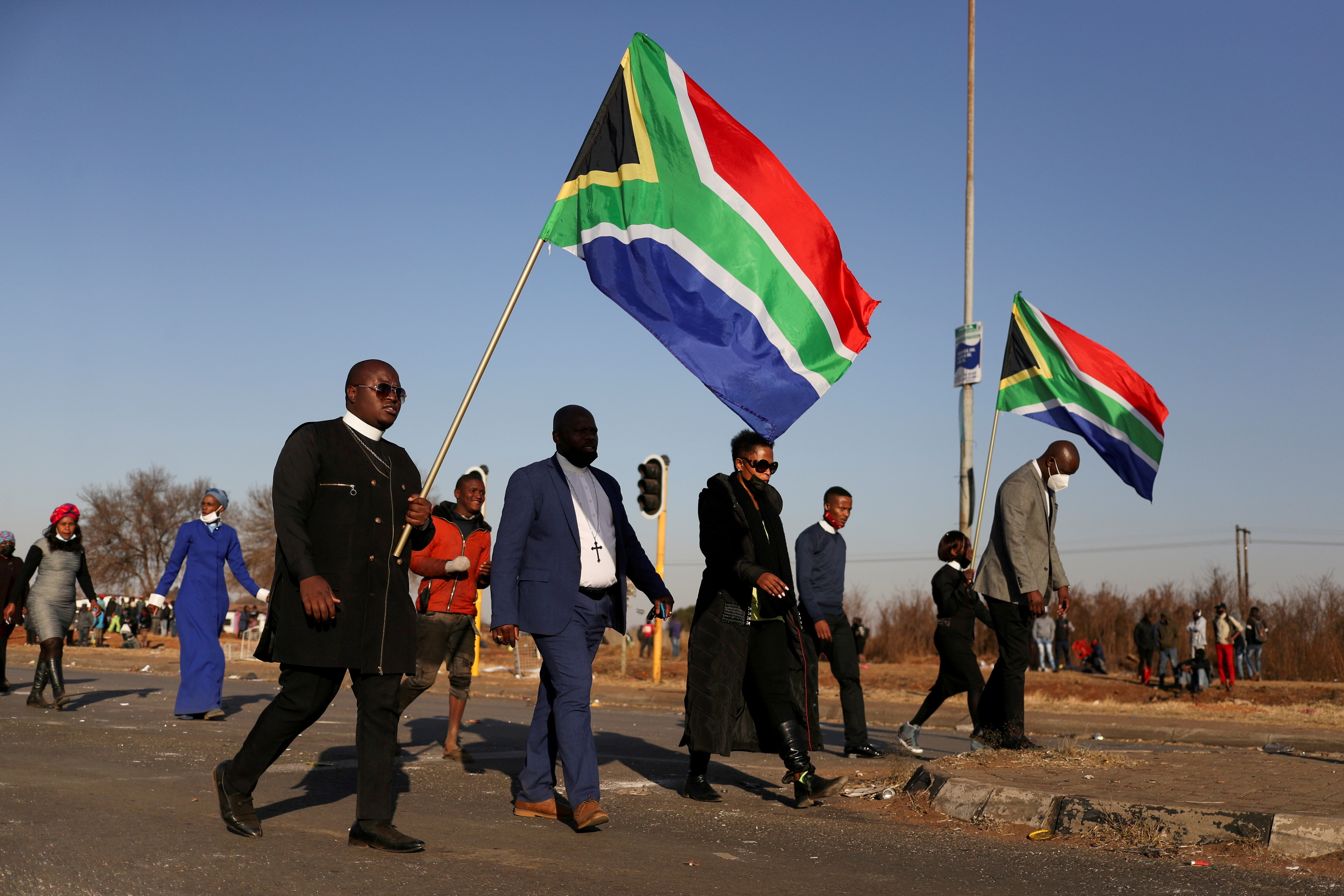 Religious leaders carrying South African flags walk near a looted shopping mall as the country deployed the army to quell unrest linked to the jailing of former South African President Jacob Zuma, in Vosloorus, South Africa, July 14, 2021. REUTERS/Siphiwe Sibeko/File Photo