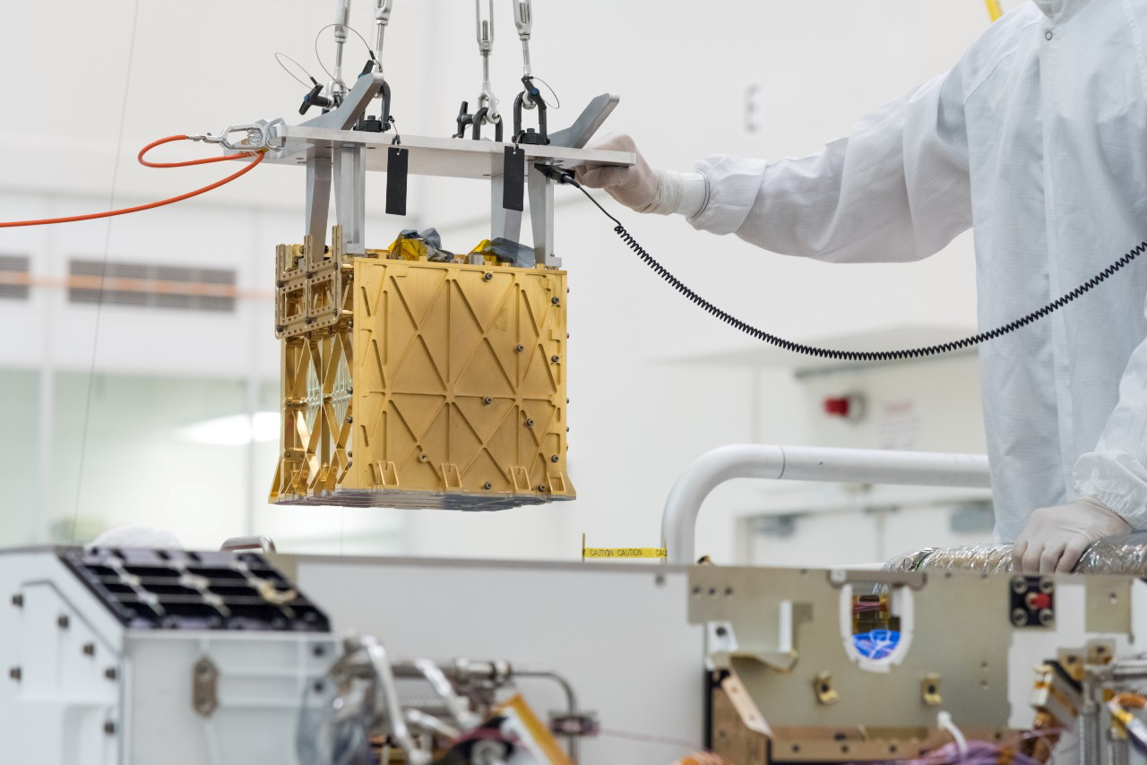 Technicians at NASA's Jet Propulsion Laboratory lower the Mars Oxygen In-Situ Resource Utilization Experiment (MOXIE) instrument into the belly of the Perseverance rover in an undated photograph in Pasadena, California, U.S. NASA/JPL-Caltech/Handout via REUTERS