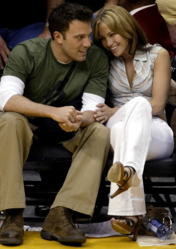 Ben Affleck gets a smile from girlfriend Jennifer Lopez  during the Los Angeles Lakers San Antonio Spurs NBA Western Conference semifinal in Los Angeles May 11, 2003.  REUTERS/Mike Blake    MB