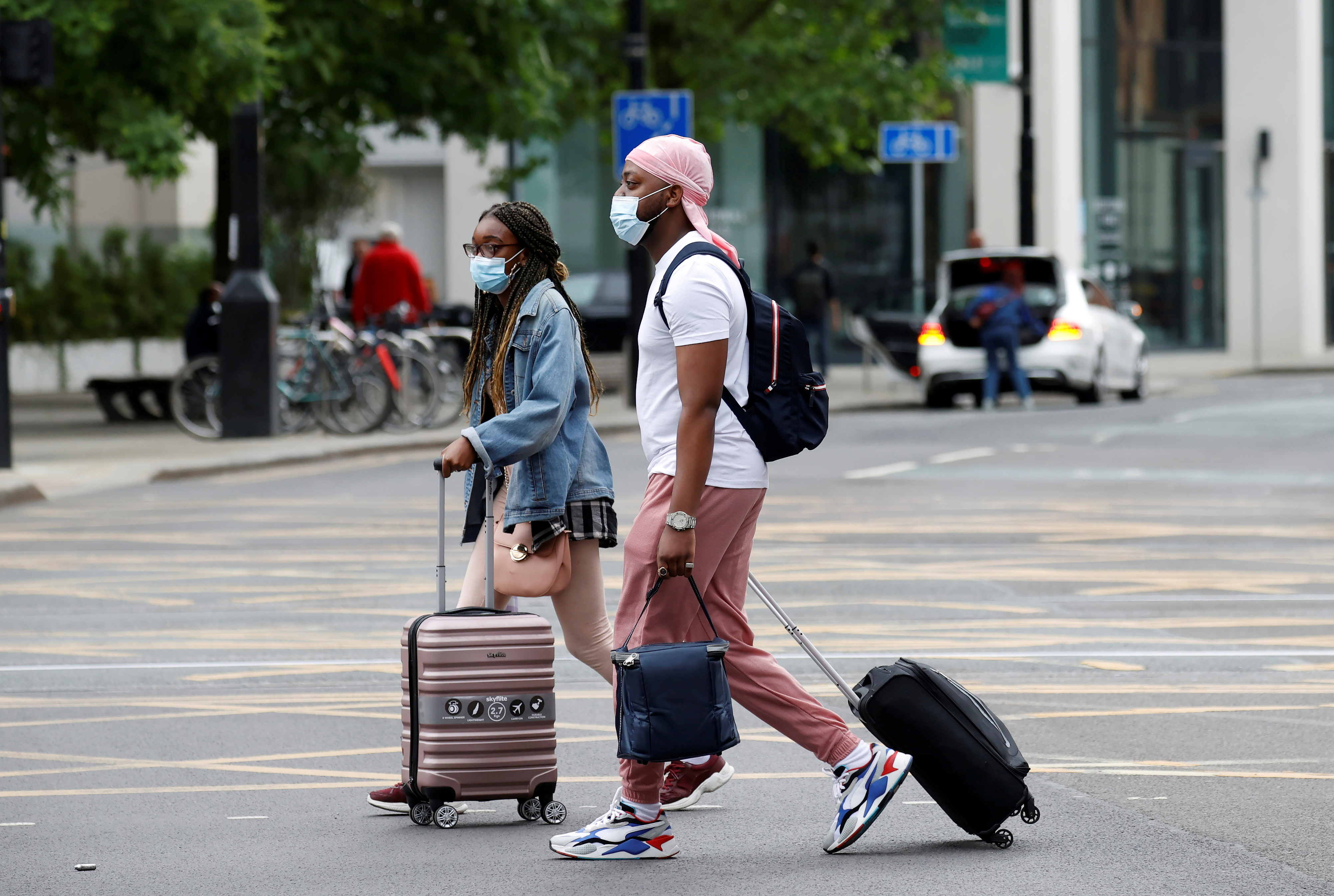 People wear protective masks as they walk with suitcases through the city centre, amid the outbreak of the coronavirus disease (COVID-19) in Manchester, Britain, June 21, 2021. REUTERS/Phil Noble