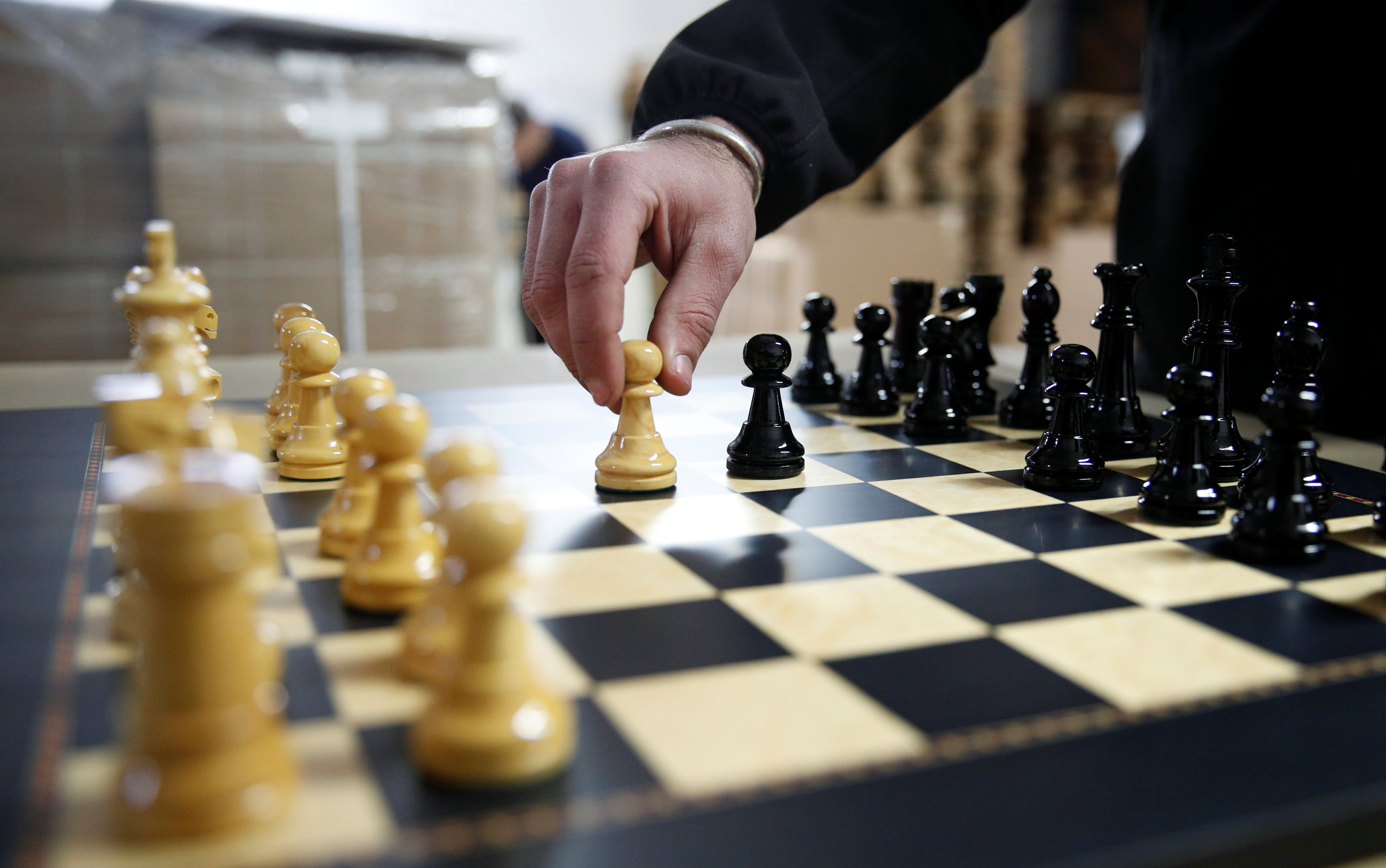David Ferrer moves a chess pawn on a chessboard at the Rechapados Ferrer factory in La Garriga, north of Barcelona, Spain, February 11, 2021. REUTERS/Albert Gea