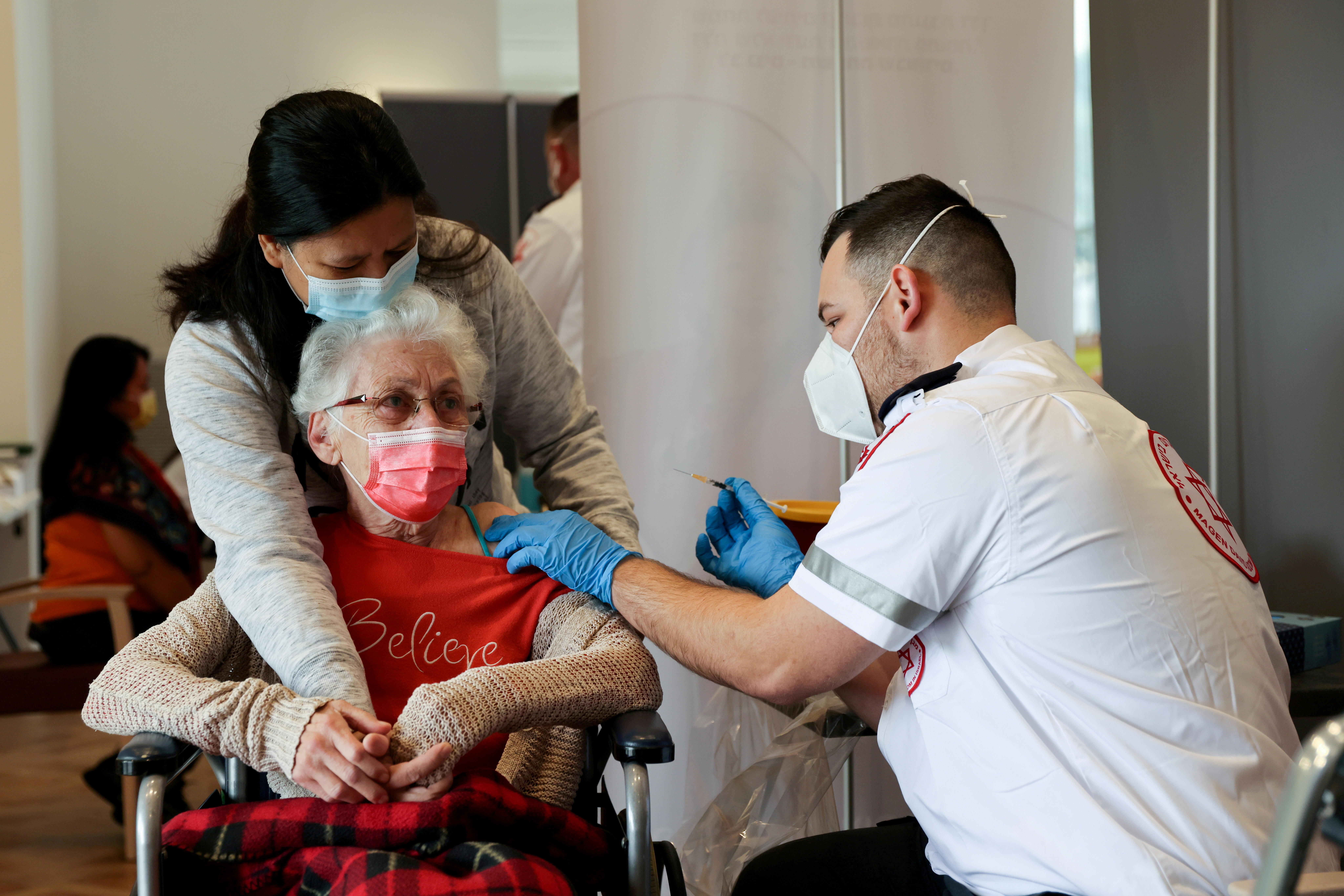 An elderly woman receives a booster shot of her vaccination against the coronavirus disease (COVID-19) at an assisted living facility, in Netanya, Israel January 19, 2021. REUTERS/Ronen Zvulun