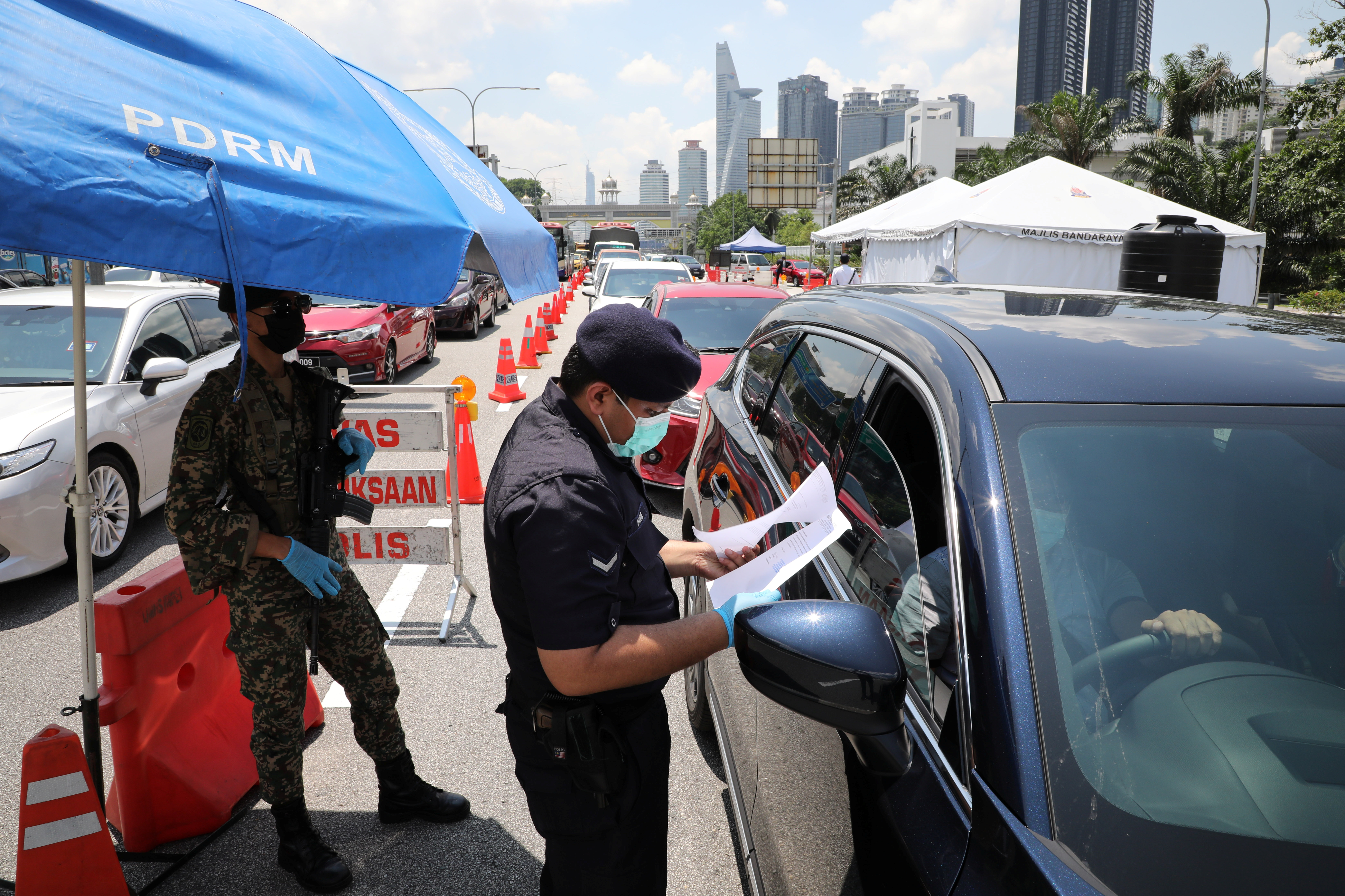 A police officer checks the documents of a driver at a roadblock during lockdown ahead of the Eid al-Fitr celebrations in an effort to prevent a large-scale transmission of the coronavirus disease (COVID-19), in Petaling Jaya, Malaysia May 10, 2021. REUTERS/Lim Huey Teng