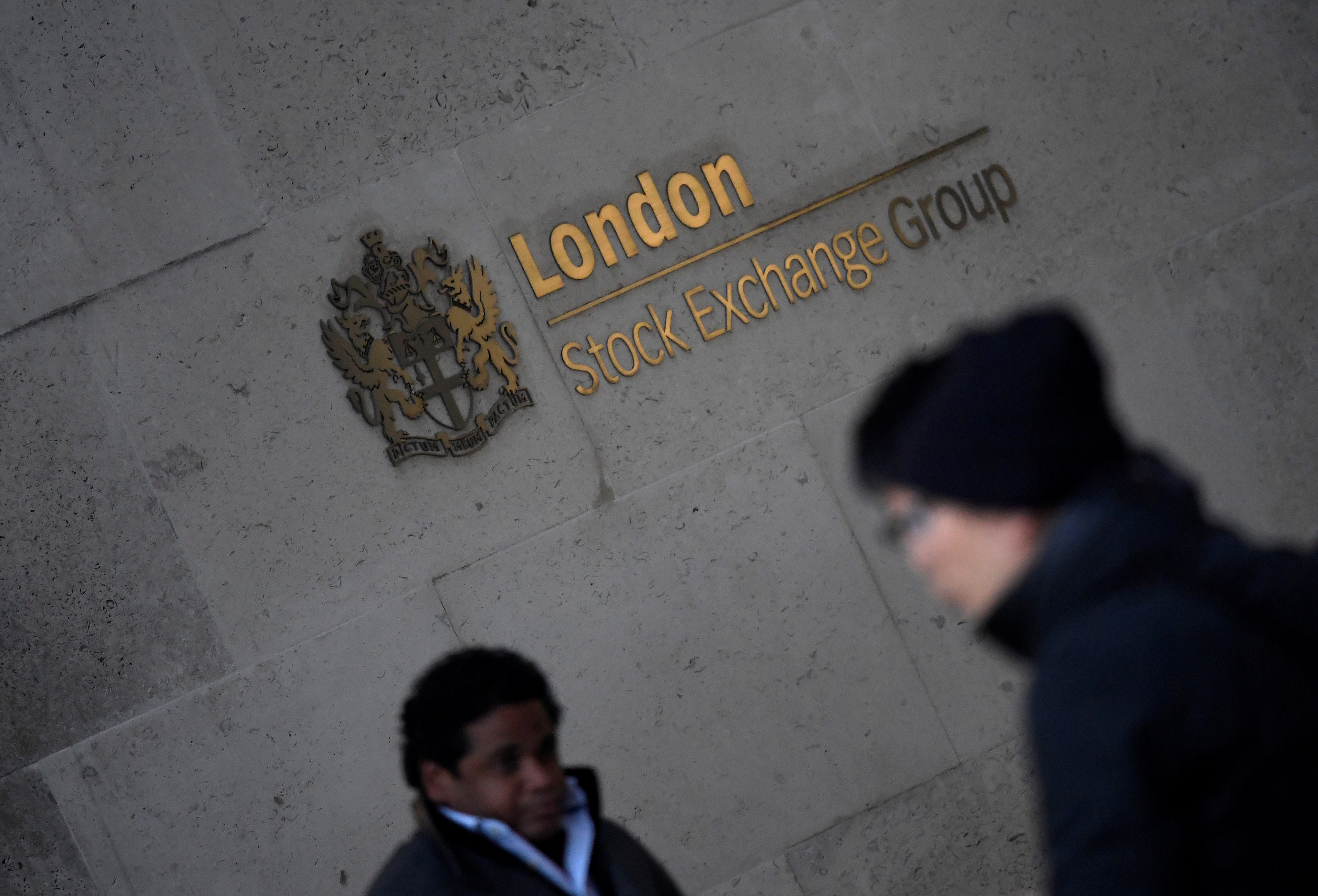 People walk past the London Stock Exchange Group offices in the City of London, Britain, December 29, 2017. REUTERS/Toby Melville/File photo
