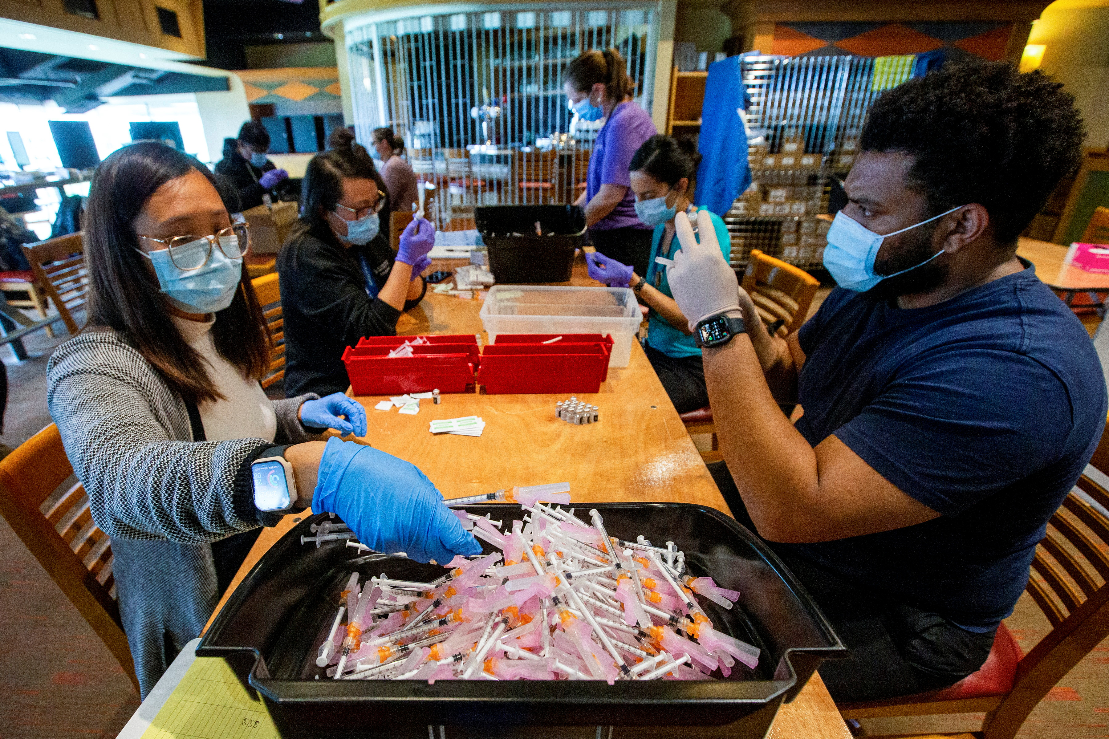 Healthcare workers prepare doses of the Pfizer/BioNTech coronavirus disease (COVID-19) vaccine, which was authorized by Canada to be used for children aged 12 to 15, at Woodbine Racetrack pop-up vaccine clinic in Toronto, Ontario, Canada May 5, 2021. REUTERS/Carlos Osorio