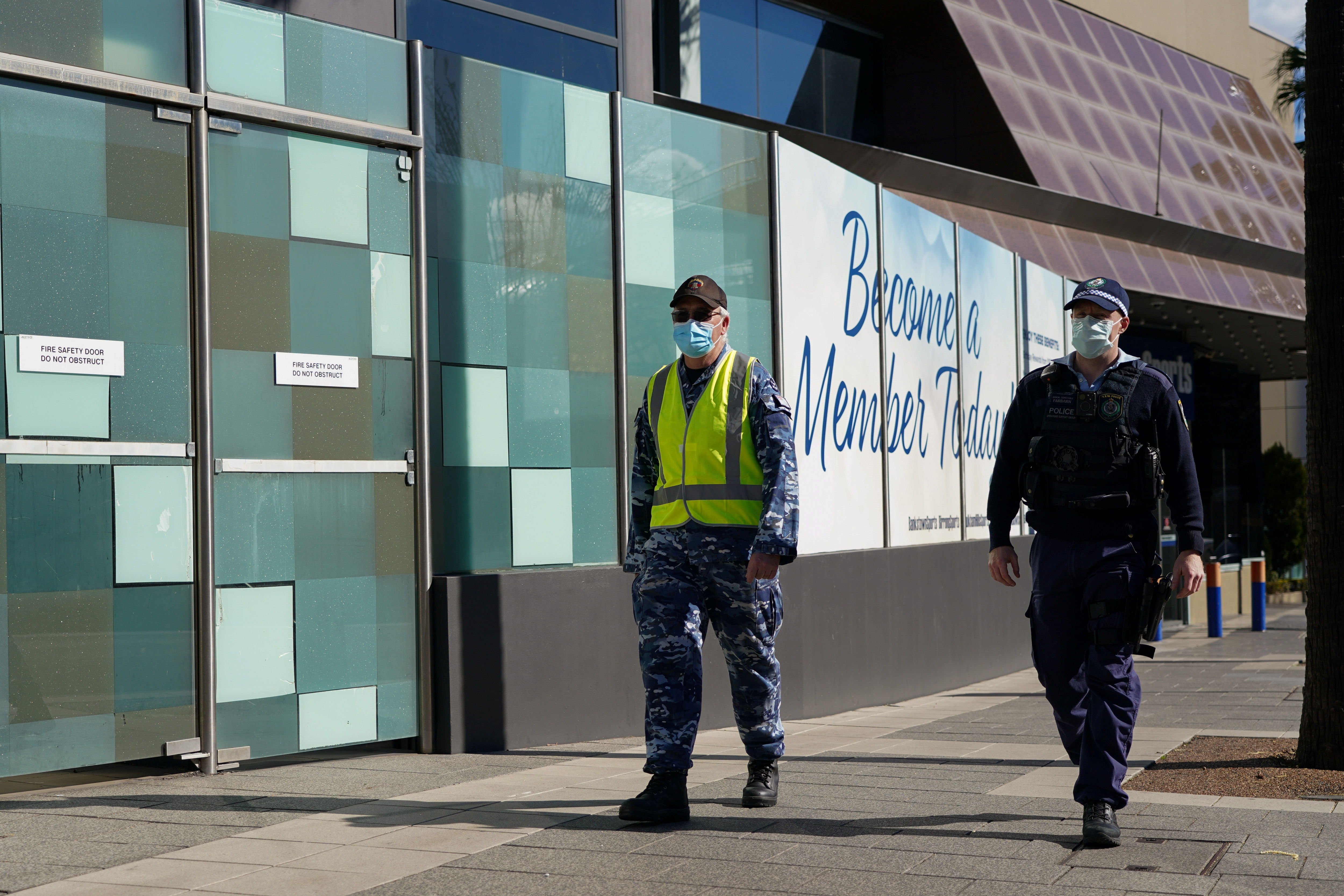 Personnel from the Australian Defence Force and New South Wales Police Force patrol a street in the Bankstown suburb during an extended lockdown to curb the spread of the coronavirus disease (COVID-19) in Sydney, Australia, August 3, 2021.  REUTERS/Loren Elliott