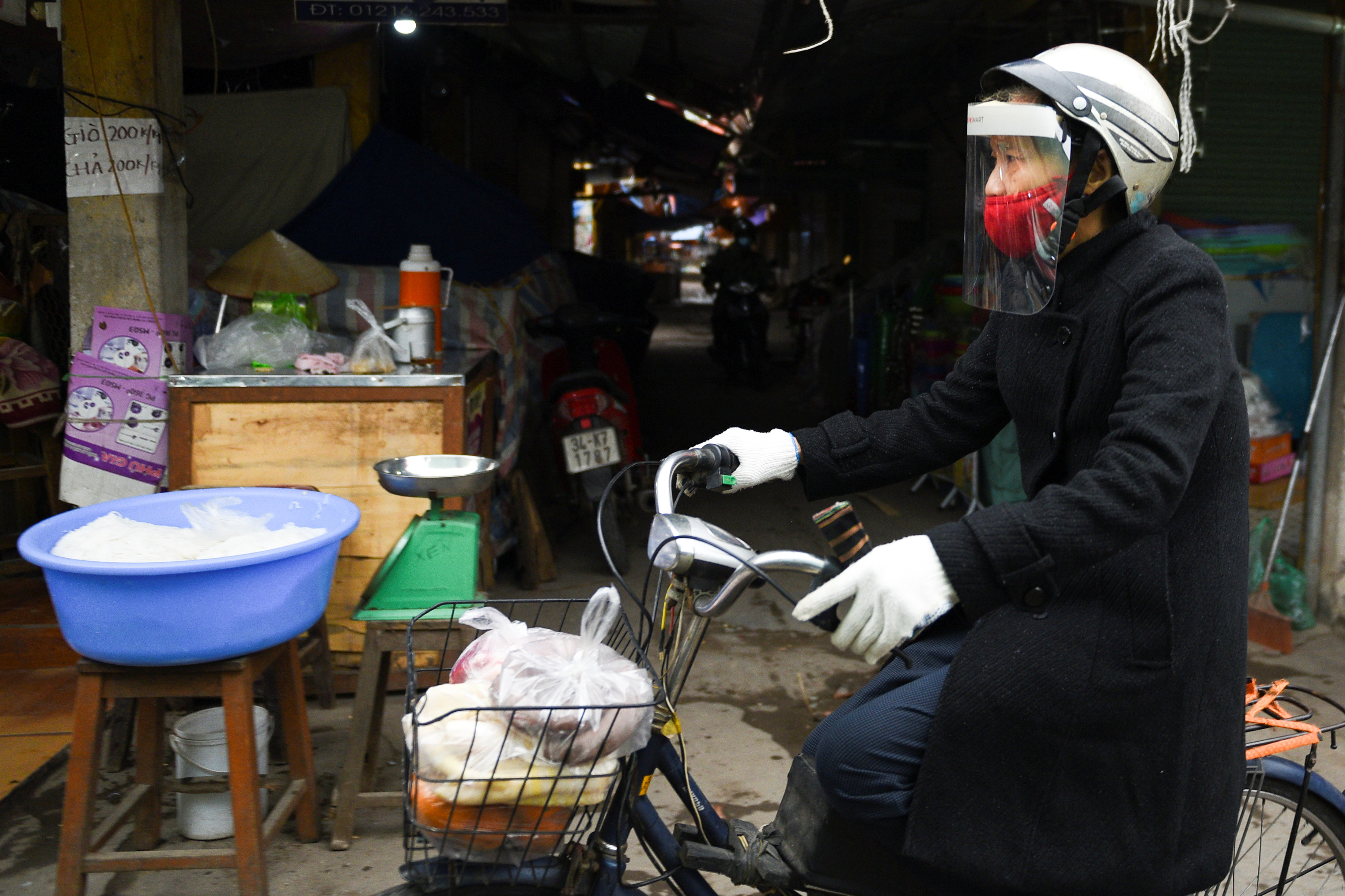 A woman wears a protective mask as she rides a bike at a market after Hai Duong authorities end 34 days of social distancing amid the spread of the coronavirus disease (COVID-19), in Chi Linh city, Hai Duong province, Vietnam, March 3, 2021. REUTERS/Thanh Hue