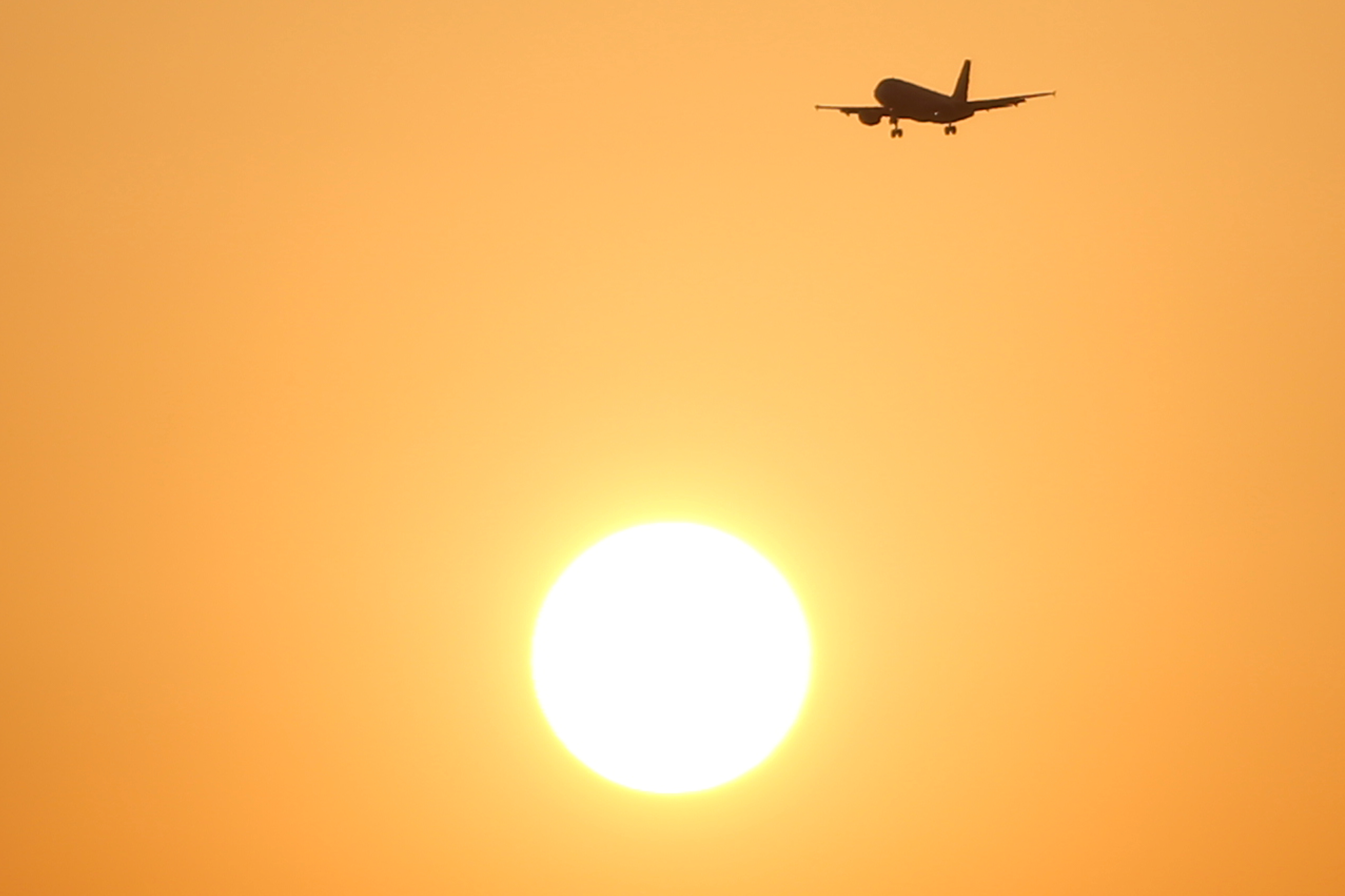 A passenger aircraft flies past the sun at sunset in Malaga, southern Spain, August 3, 2018. REUTERS/Jon Nazca/Files