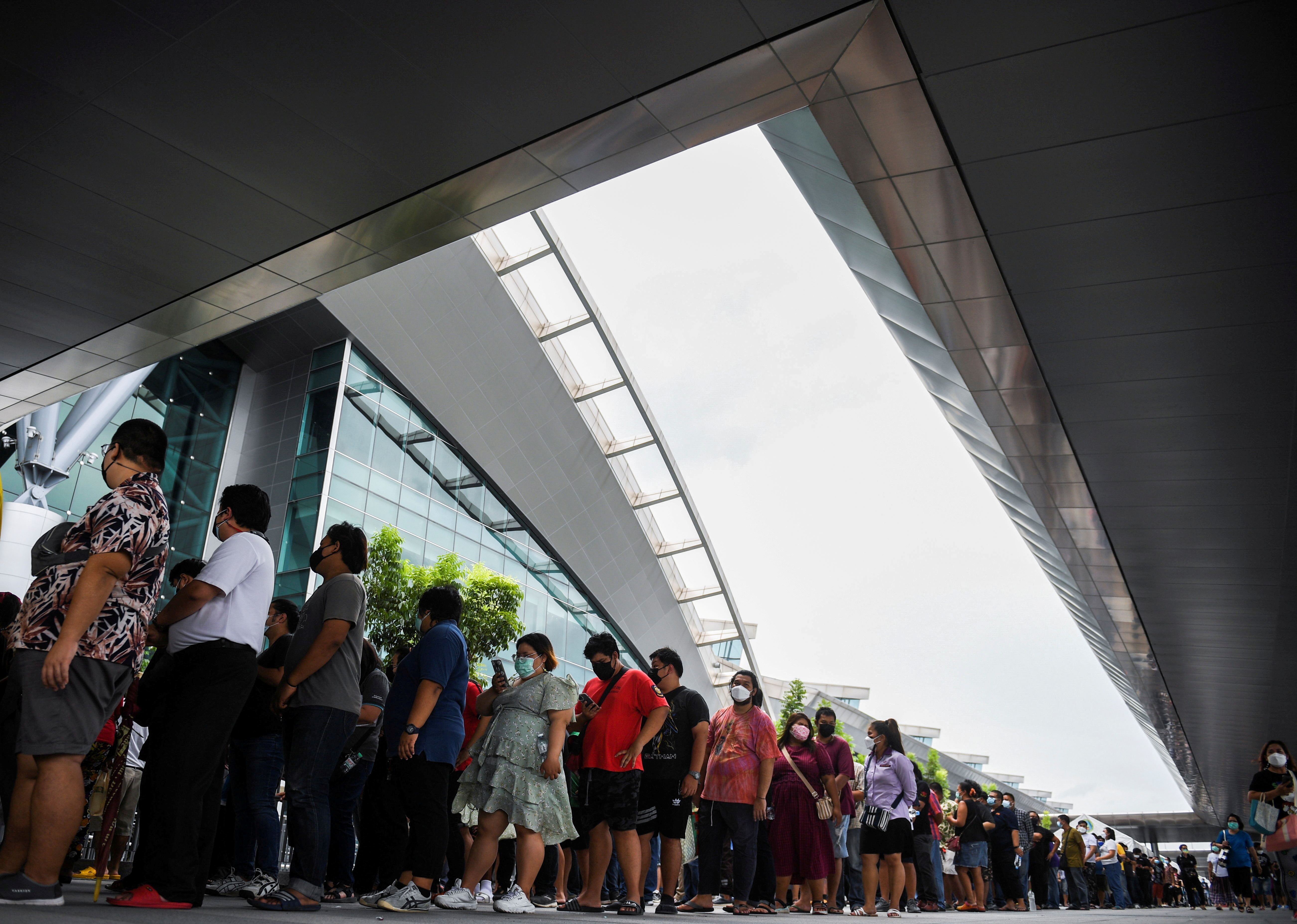 People wearing masks queue outside the Central Vaccination Center as Thailand opens walk-in first dose of the AstraZeneca coronavirus (COVID-19) vaccination scheme for elders, people with a minimum weight of 100 kg and pregnant women in Bangkok, Thailand, July 22, 2021. REUTERS/Chalinee Thirasupa