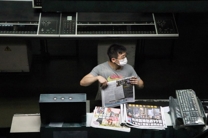 An employee works at the printing facility of Apple Daily newspaper after police raided its newsroom and arrested five executives, in Hong Kong, China early June 18, 2021. REUTERS/Jessie Pang