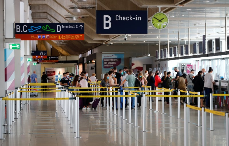 Travellers line up at a check-in counter of the Cologne-Bonn Airport, as the spread of the coronavirus disease (COVID-19) continues, in Cologne, July 28, 2020.  REUTERS/Wolfgang Rattay