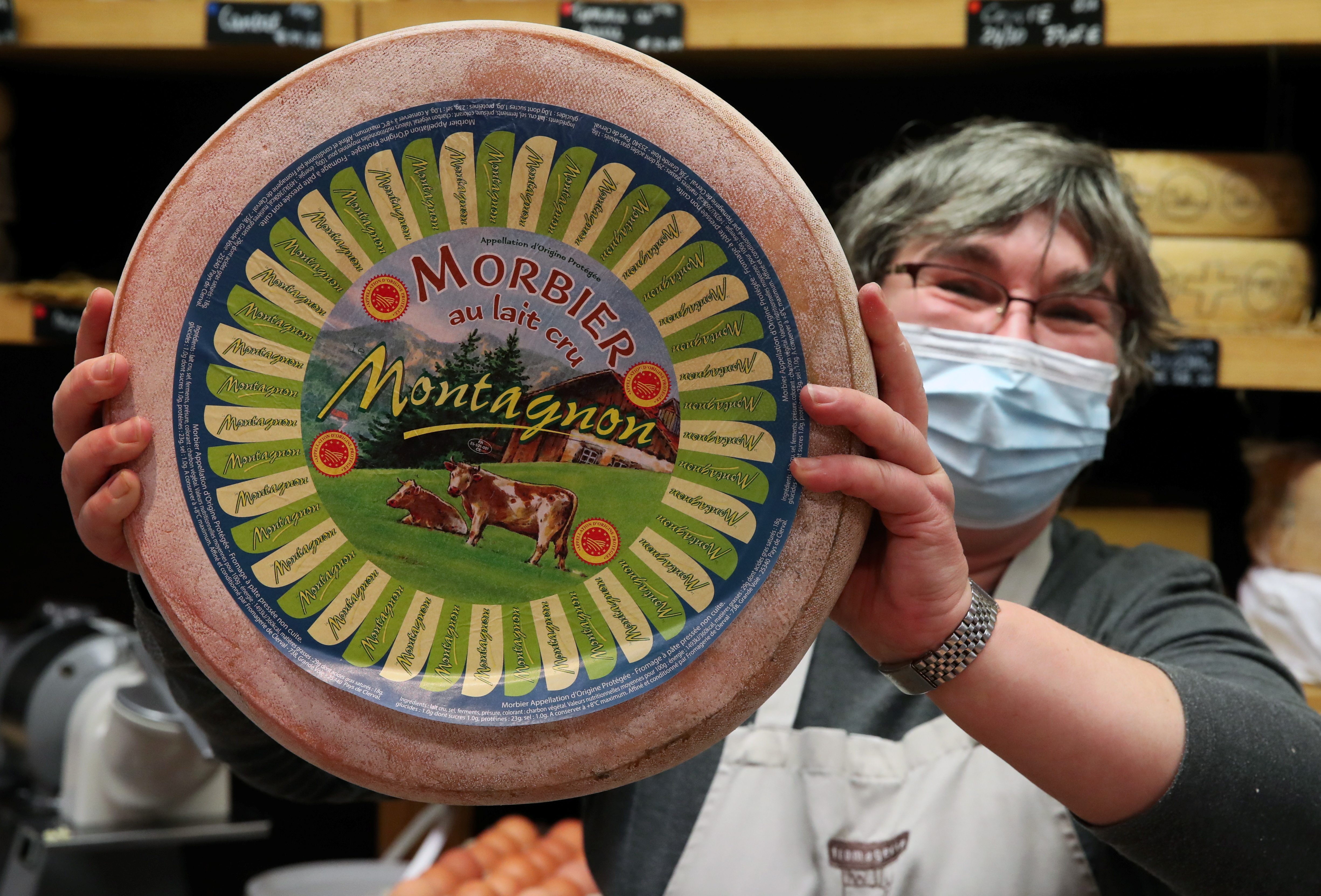 The owner of a shop specialised in cheeses shows a wheel of Morbier cheese, in Brussels, Belgium December 17, 2020. REUTERS/Yves Herman