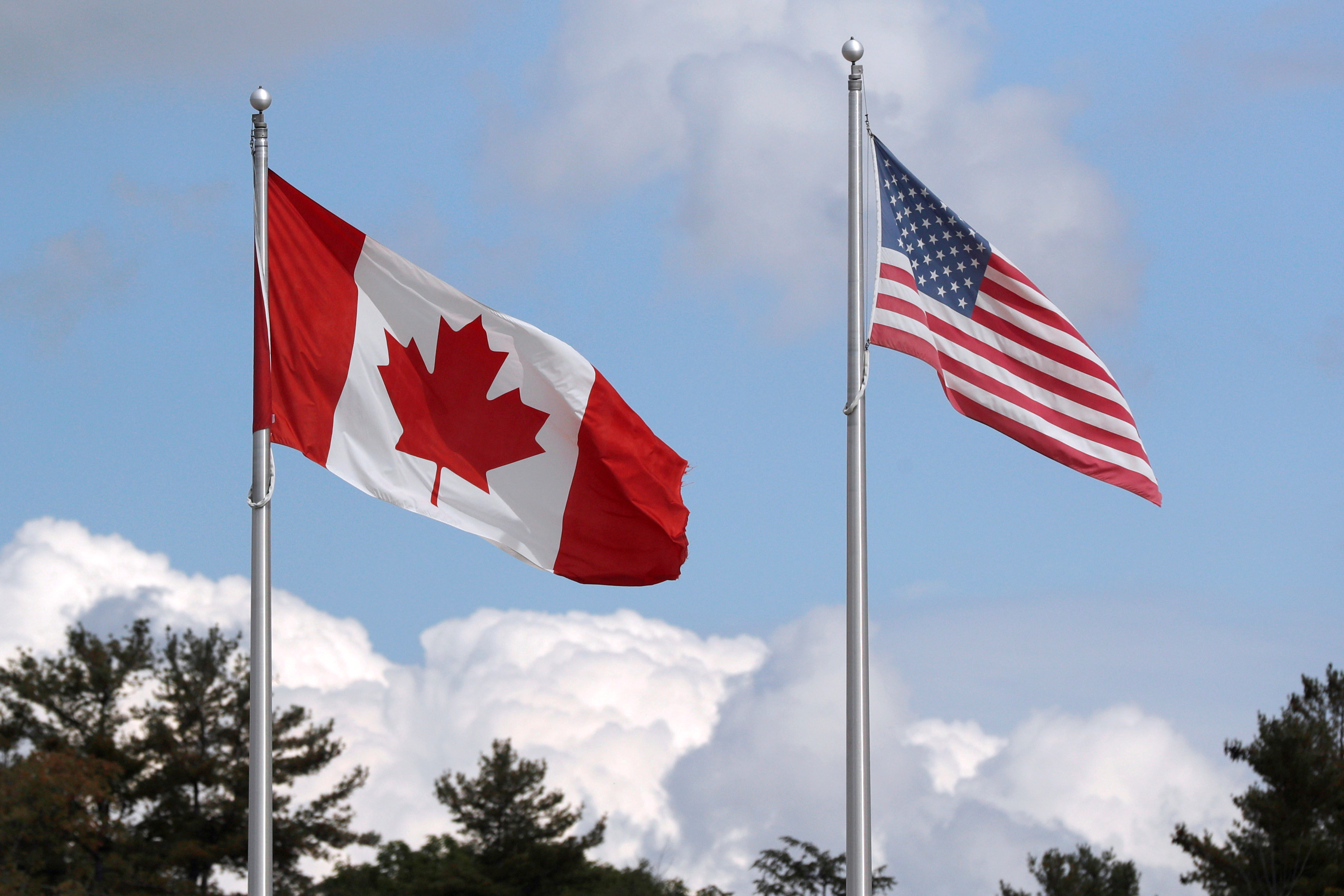 A U.S. and a Canadian flag flutter at the Canada-United States border crossing at the Thousand Islands Bridge, which remains closed to non-essential traffic to combat the spread of the coronavirus disease (COVID-19) in Lansdowne, Ontario, Canada September 28, 2020.  REUTERS/Lars Hagberg/File Photo