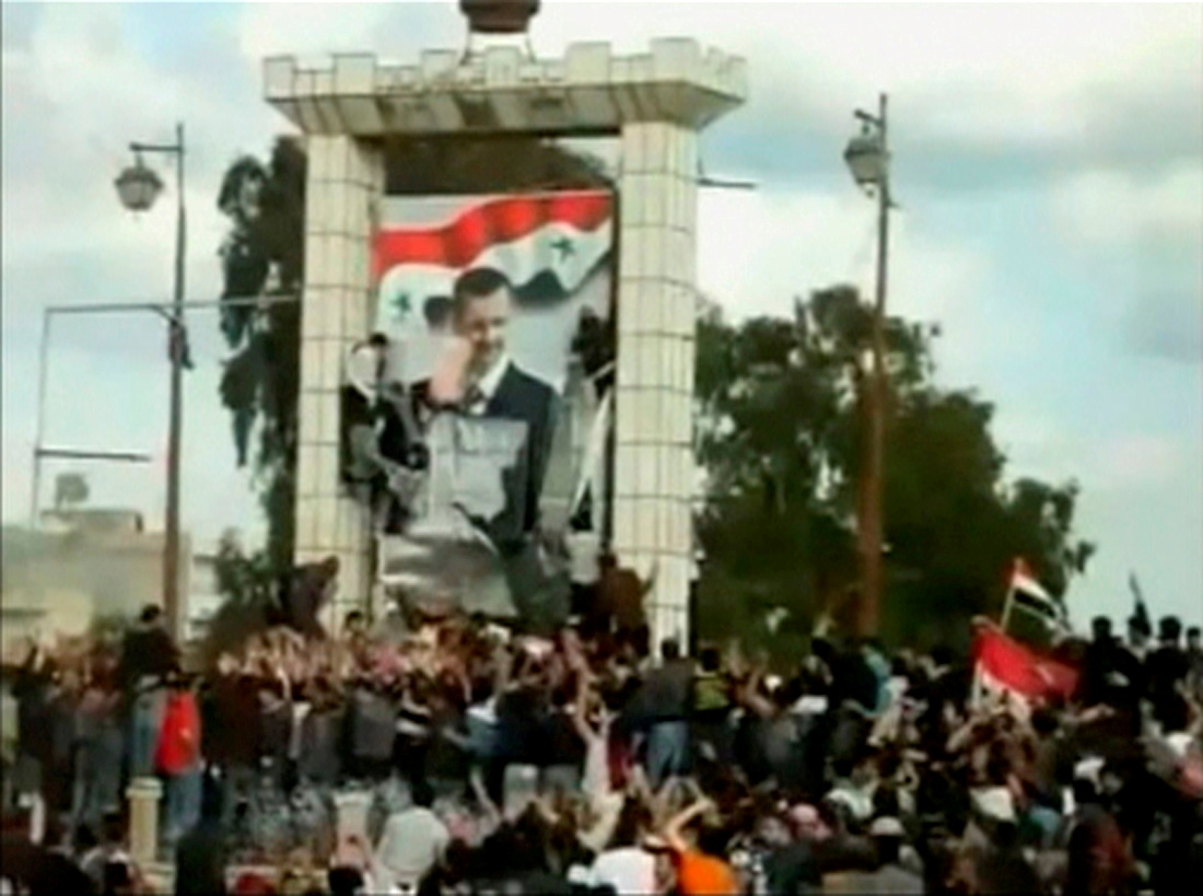 This still image taken from amateur video shows protesters defacing a giant poster of Syria's President Bashar al-Assad in Deraa March 25, 2011.  REUTERS IS UNABLE TO INDEPENDENTLY VERIFY THIS IMAGE.  REUTERS/Amateur Video via Reuters TV/File Photo