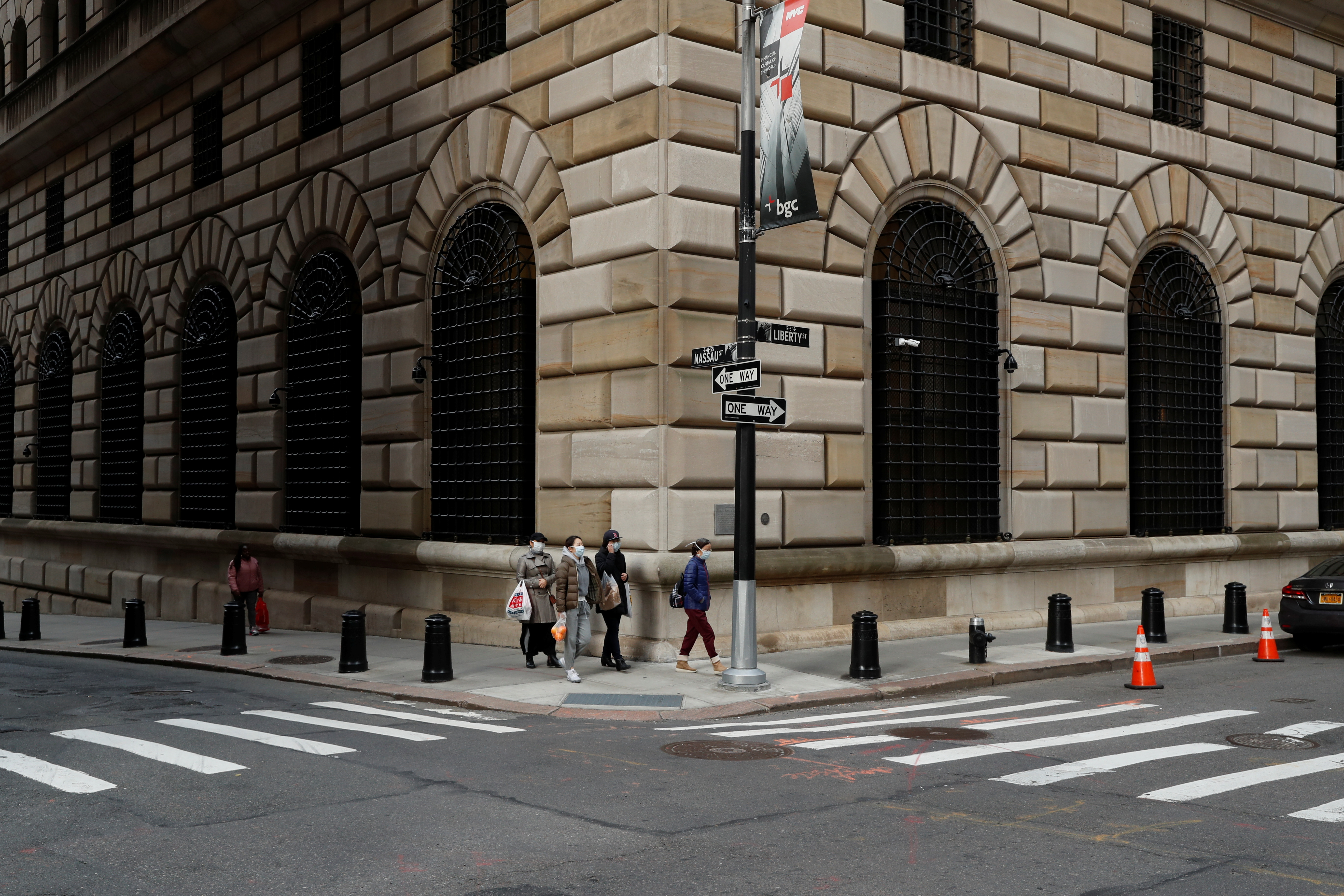 People walk wearing masks outside The Federal Reserve Bank of New York in New York City, U.S., March 18, 2020. REUTERS/Lucas Jackson/File Photo