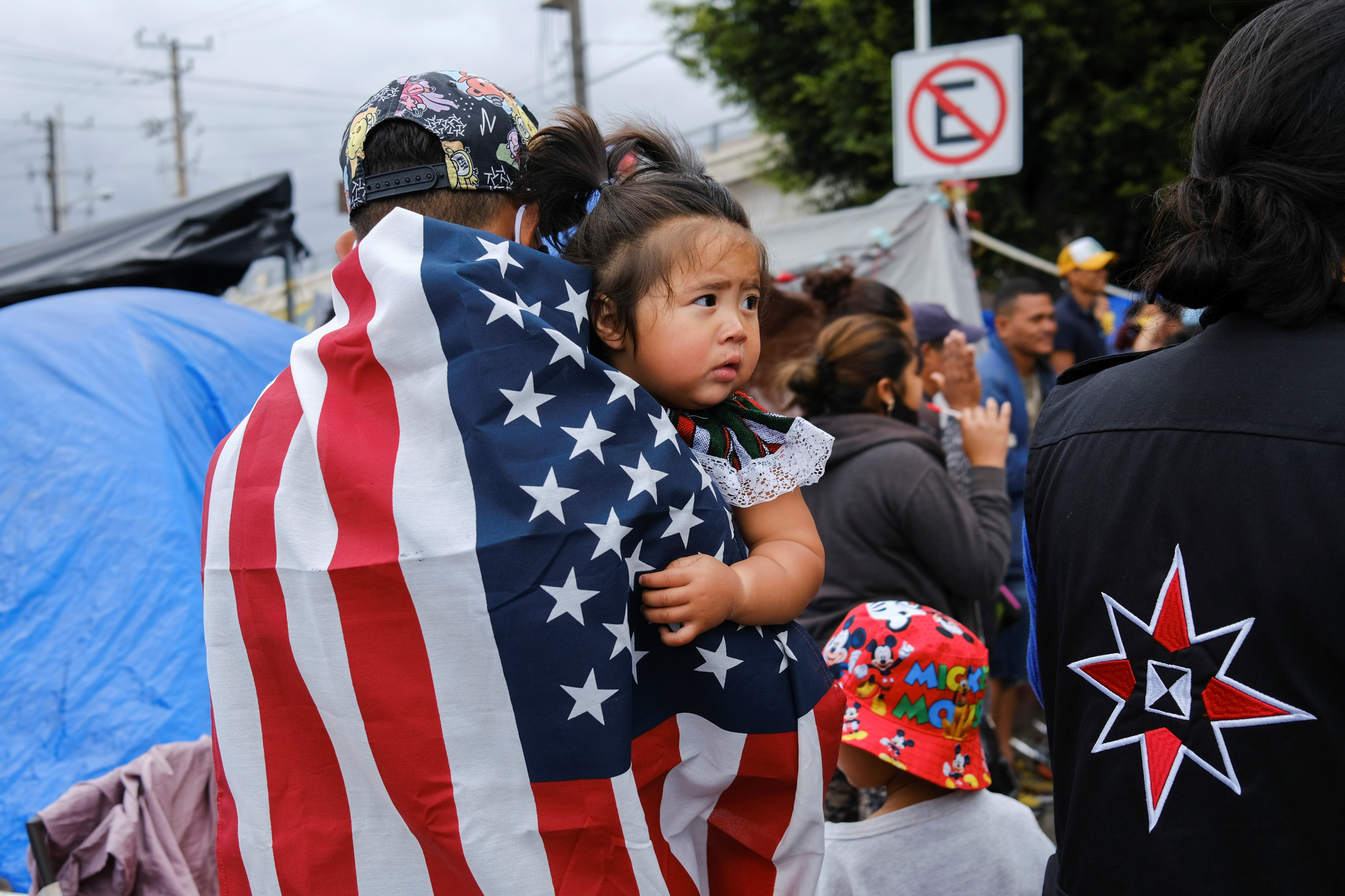 Honduran migrant Kevin, wearing a U.S. flag, holds his daughter Keiry, during a multicultural activity at a makeshift camp at the El Chaparral border port of entry with the U.S., in Tijuana, Mexico April 22, 2021.  REUTERS/Toya Sarno Jordan