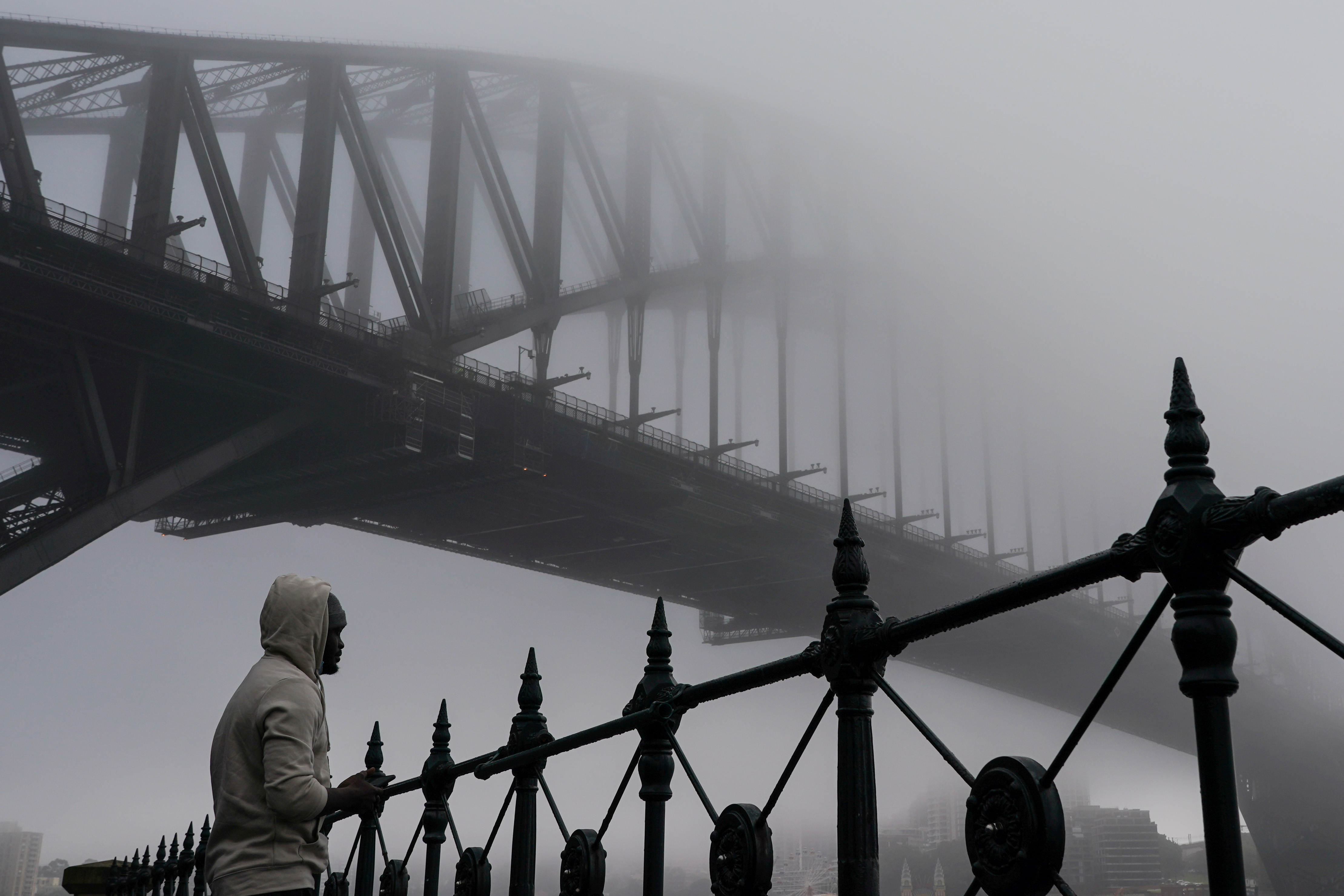 A man takes in the waterfront view underneath the Sydney Harbour Bridge, seen shrouded in fog, during a lockdown to curb the spread of a coronavirus disease (COVID-19) outbreak in Sydney, Australia, June 30, 2021. REUTERS/Loren Elliott