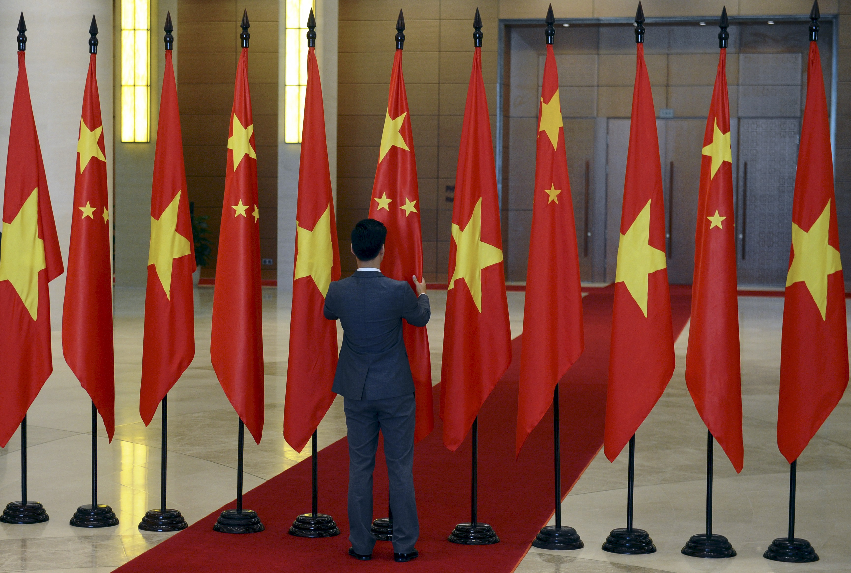 A Vietnamese protocol officer arranges Chinese and Vietnamese flags before the arrival of Chinese President Xi Jinping at the Parliament House in Hanoi, Vietnam November 6, 2015. REUTERS/Hoang Dinh Nam/Pool/Files
