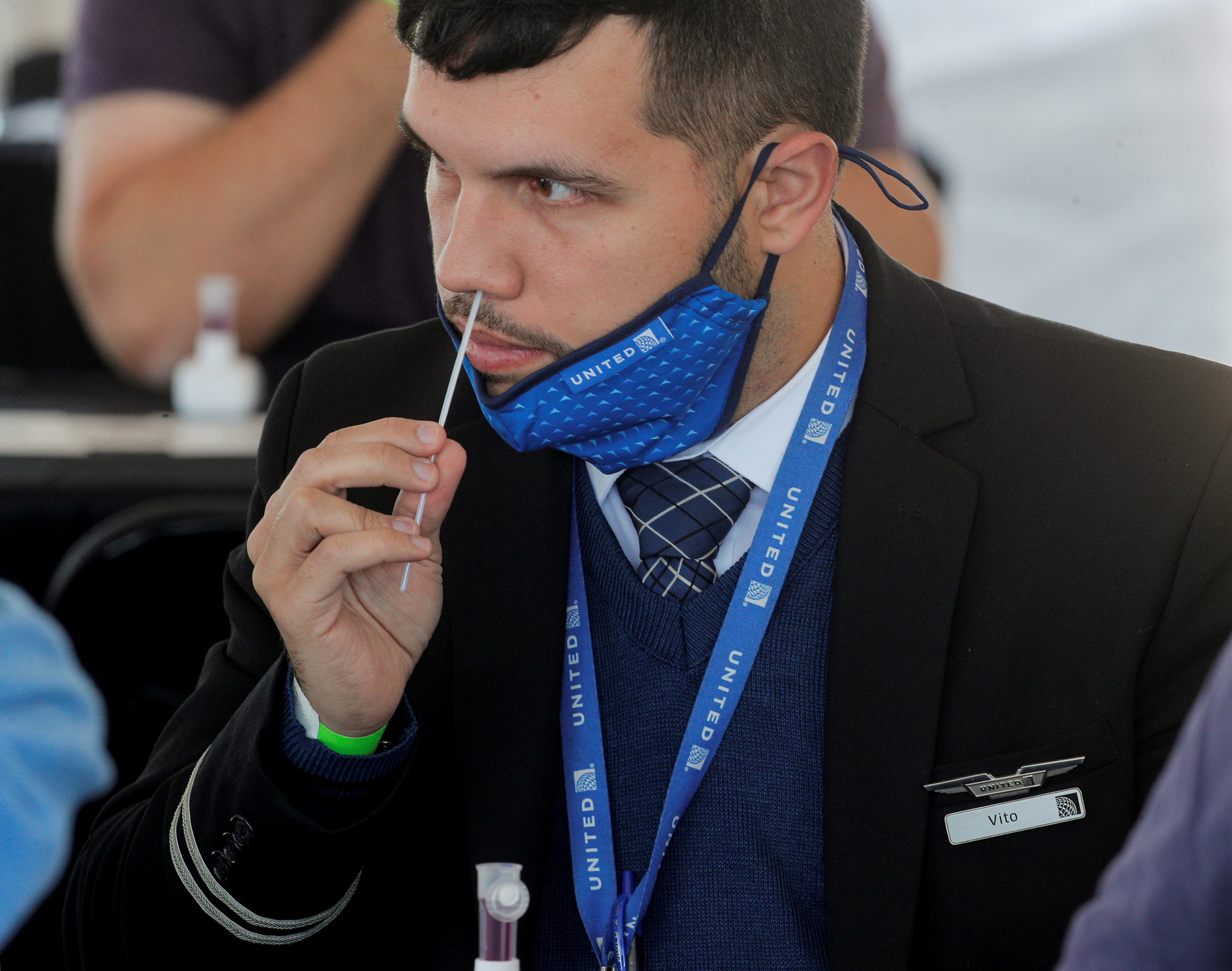 A United Airlines employee swabs his nose for a coronavirus disease (COVID-19) testat MetLife Stadium in East Rutherford, New Jersey, U.S., May 6, 2021. REUTERS/Brendan McDermid