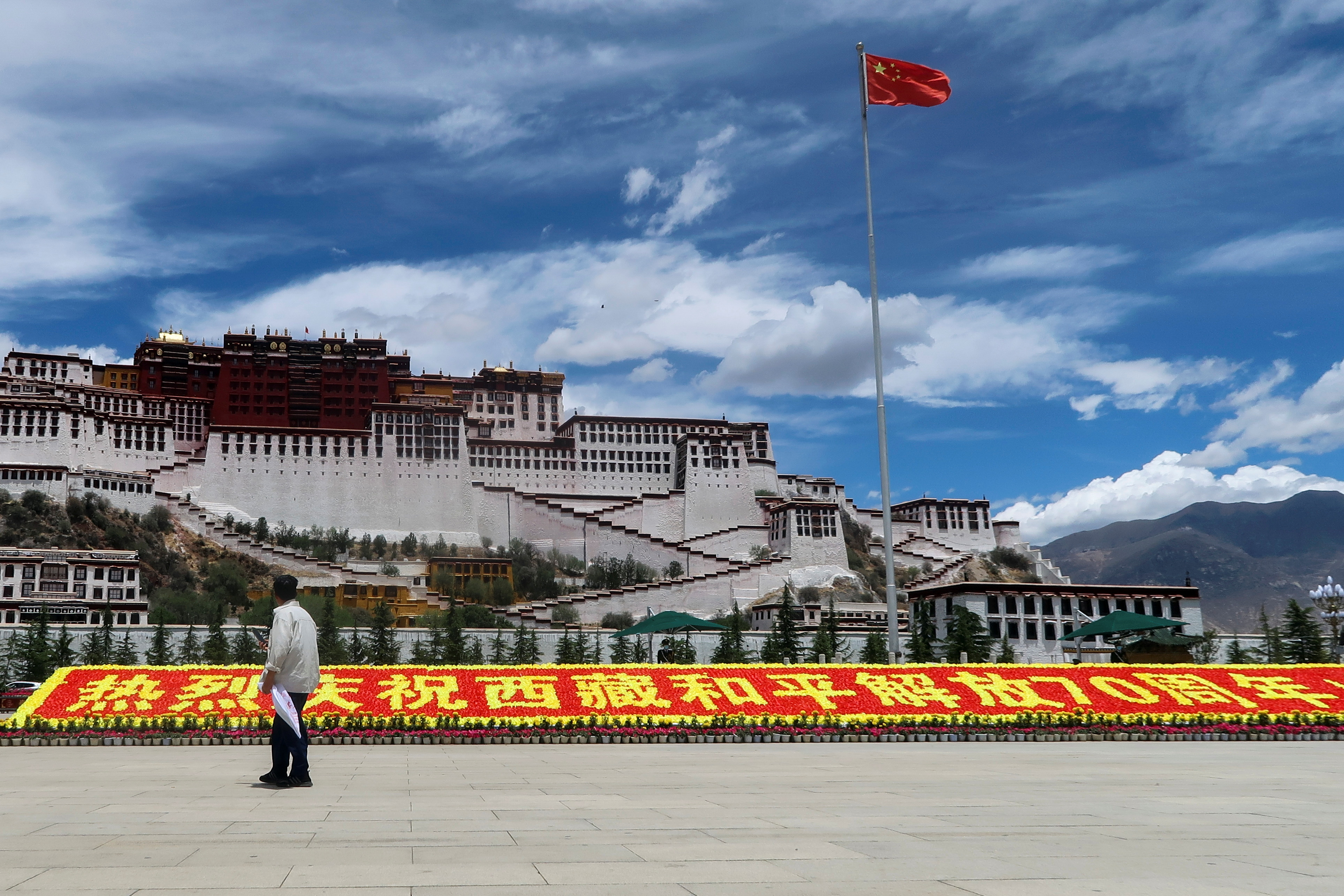 A man stands in front of a sign marking 70 years since Chinese rule over Tibet Autonomous Region, on the Potala Palace Square during a government-organised media tour to Lhasa, Tibet Autonomous Region, China June 1, 2021. Picture taken June 1, 2021. REUTERS/Martin Pollard