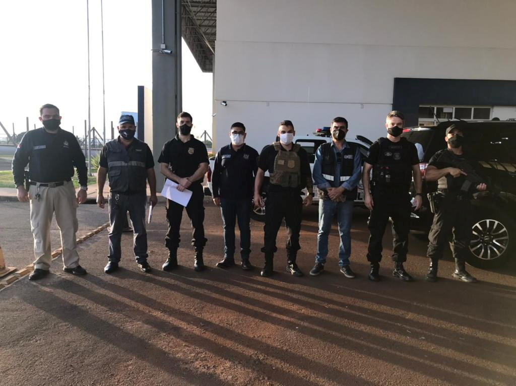 Personnel of the General Directorate of Migration, agents of the Paraguayan office of INTERPOL and members of the Federal Police of Brazil pose for a photo, during the handover of Brazilian citizen Chelbe Willams Moraes in an unknown location, June 7, 2021. Courtesy of Direccion General De Migraciones  Paraguay/Handout via REUTERS/Files