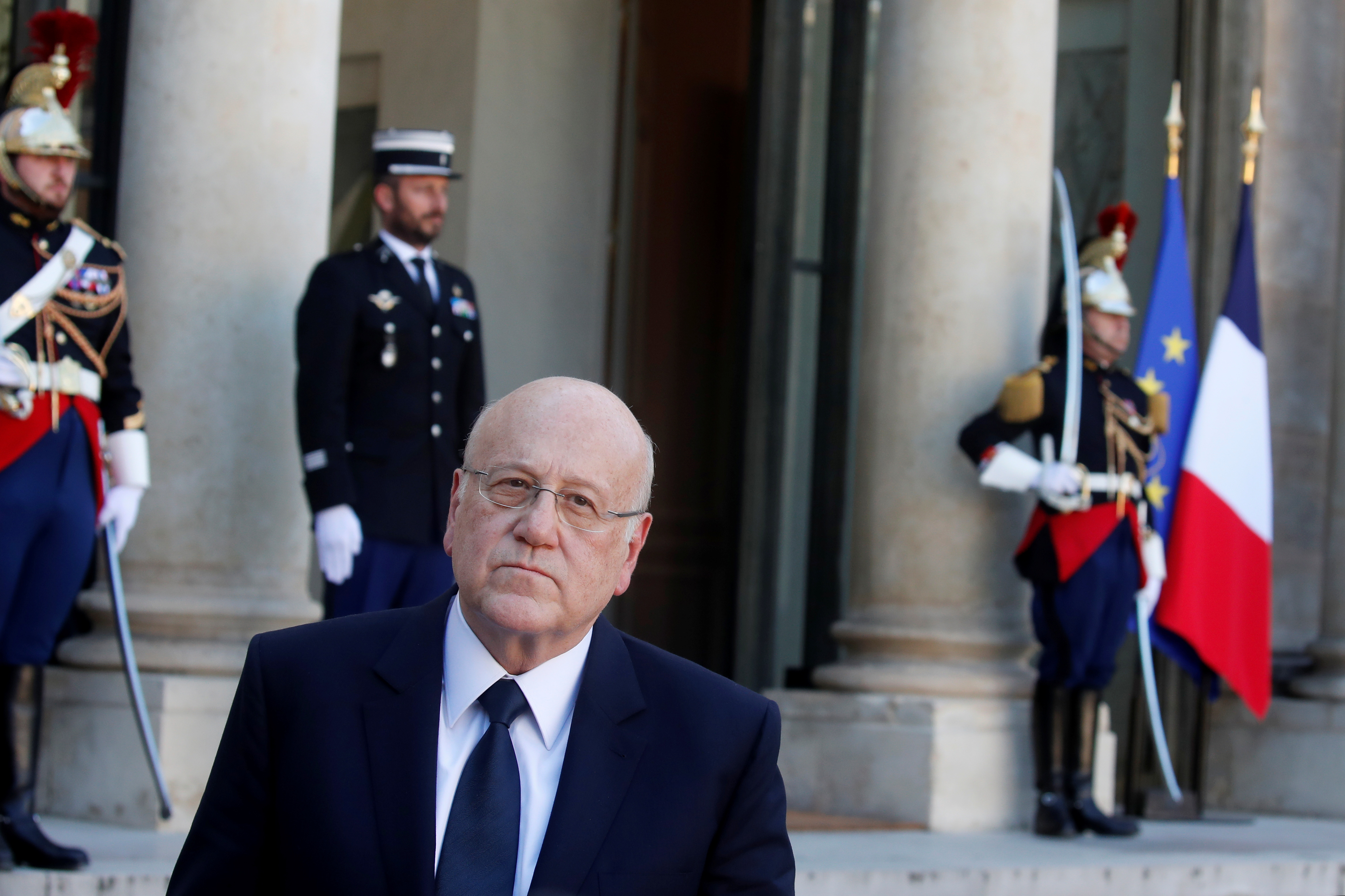 Lebanon's Prime Minister Najib Mikati listens to French President Emmanuel Macron (not seen) as they deliver a joint statement after a working lunch at the Elysee Palace in Paris, France, September 24, 2021. REUTERS/Gonzalo Fuentes