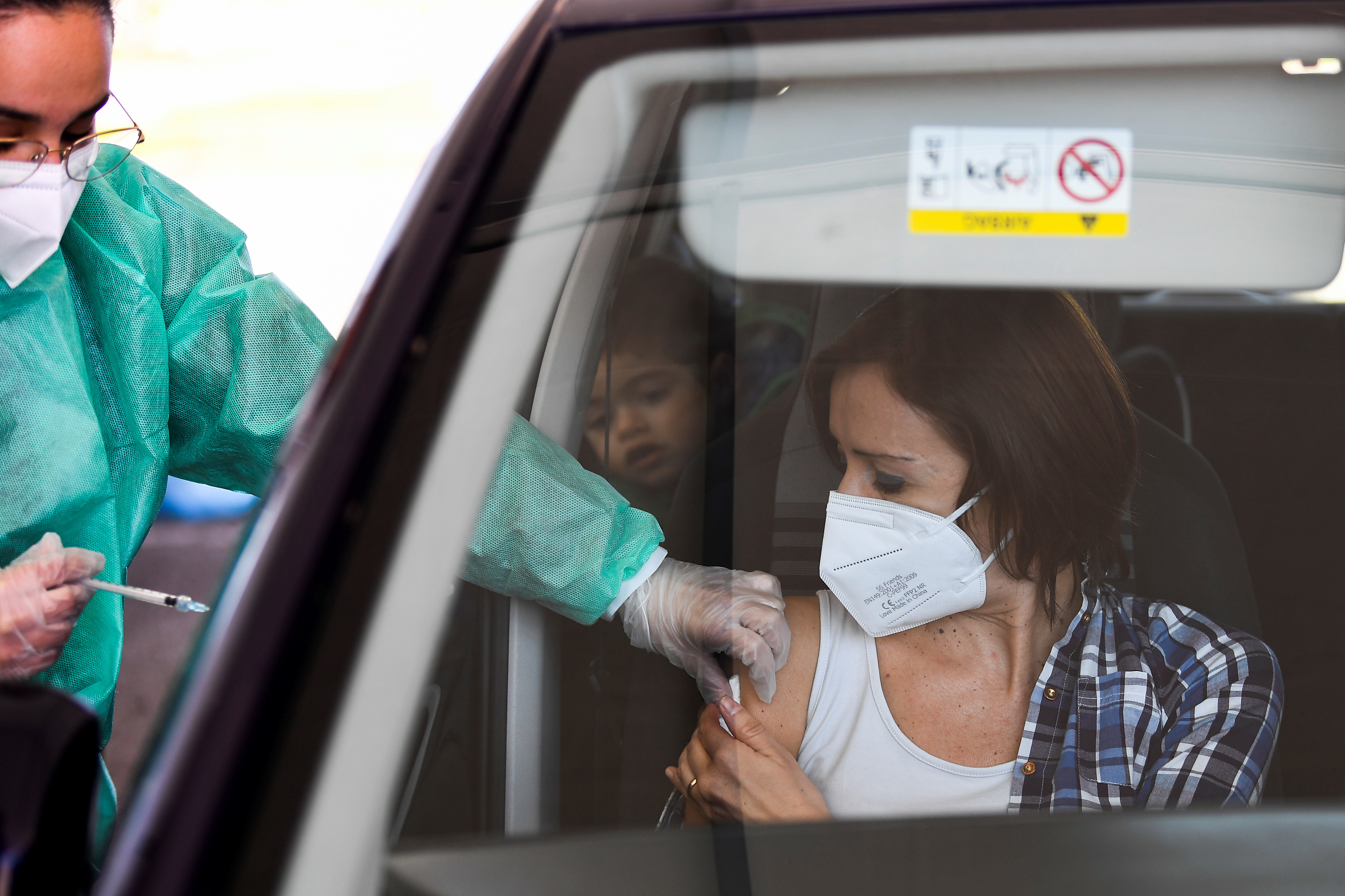 A woman receives the AstraZeneca vaccination against the coronavirus disease (COVID-19) at a drive-through site, in Milan, Italy, March 15, 2021. REUTERS/Flavio Lo Scalzo