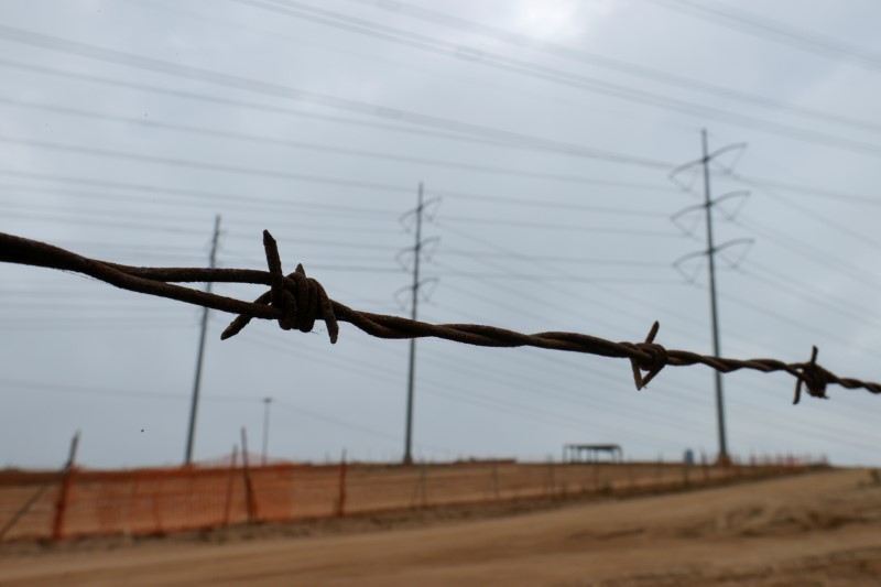 A barbed-wire fence runs parallel to power power lines as California consumers prepare for more possible outages following weekend outages to reduce system strain during a brutal heat wave amid the outbreak of coronavirus disease (COVID-19) in Carlsbad, California, U.S., August 17, 2020.      REUTERS/Mike Blake