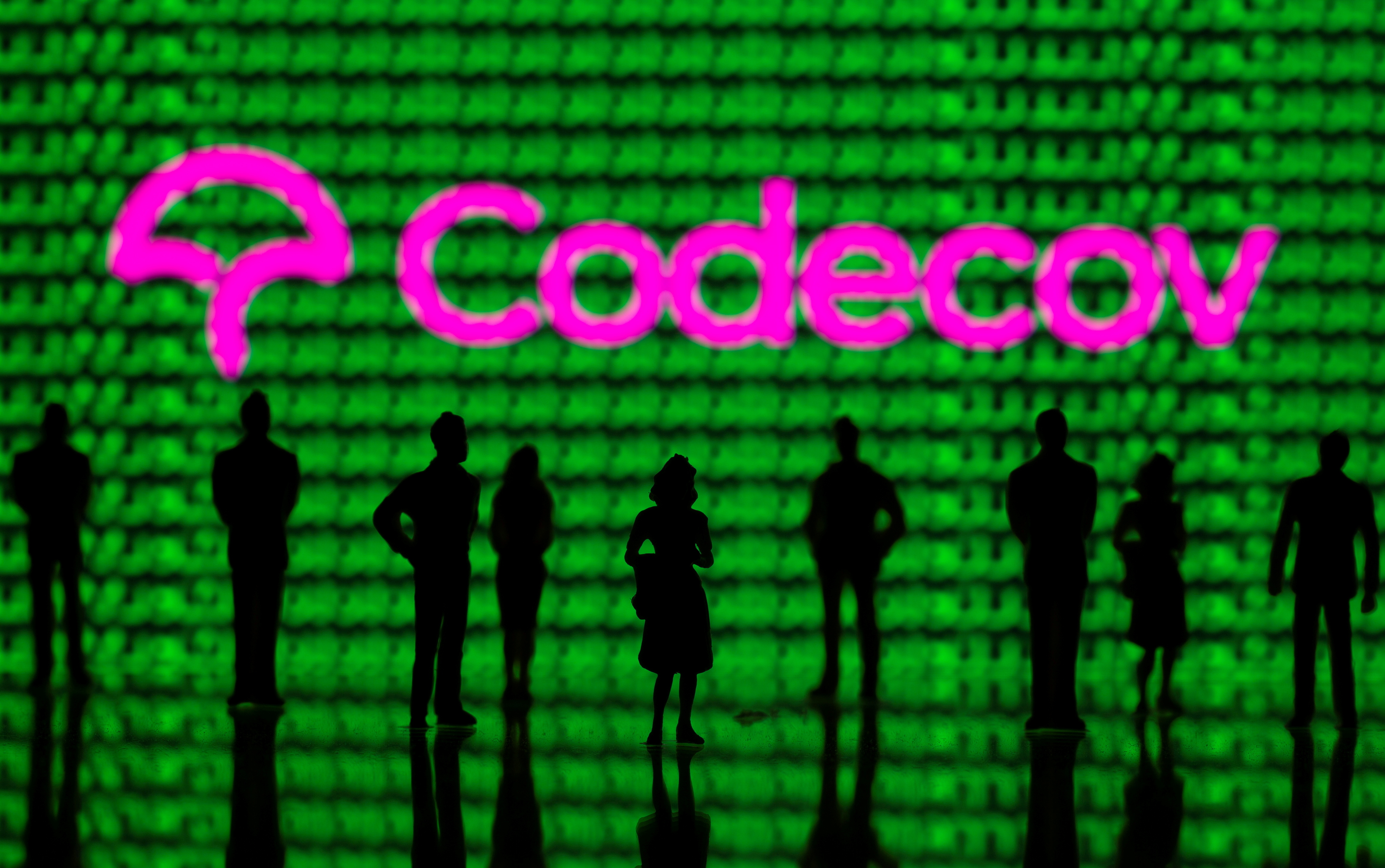 Small toy figures are seen in front of the Codecov logo and cyber binary codes in this illustration taken April 20, 2021. REUTERS/Dado Ruvic/Illustration