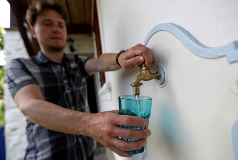 Milan Starec pours a glass of water from a tap at his home in the village of Uhelna near the town of Hradek nad Nisou, Czech Republic, June 15, 2021. REUTERS/David W Cerny