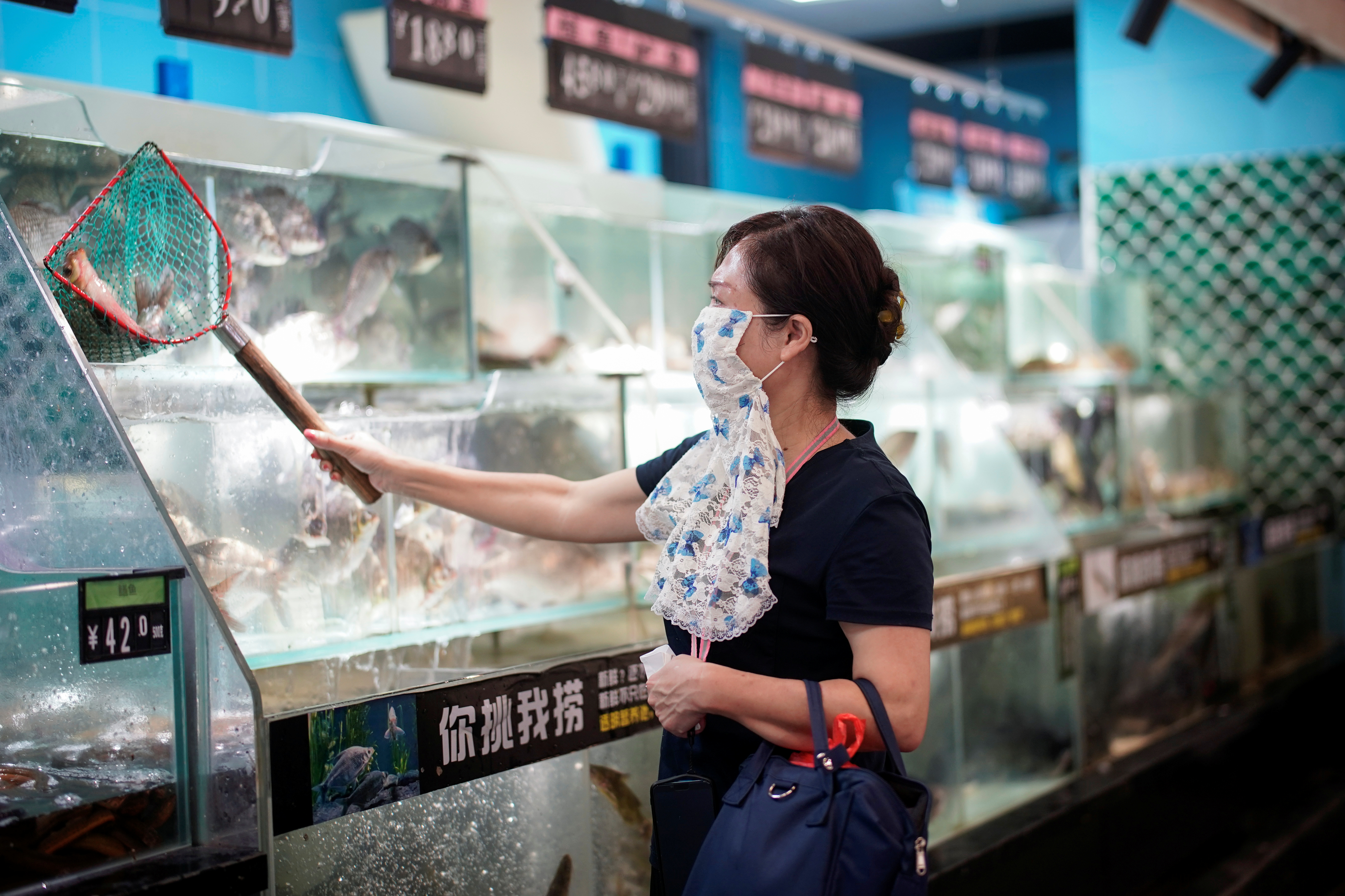 A woman buys live fish at a supermarket during a government-organized media tour following the coronavirus disease (COVID-19) outbreak, in Wuhan, Hubei province, China, September 4, 2020. REUTERS/Aly Song