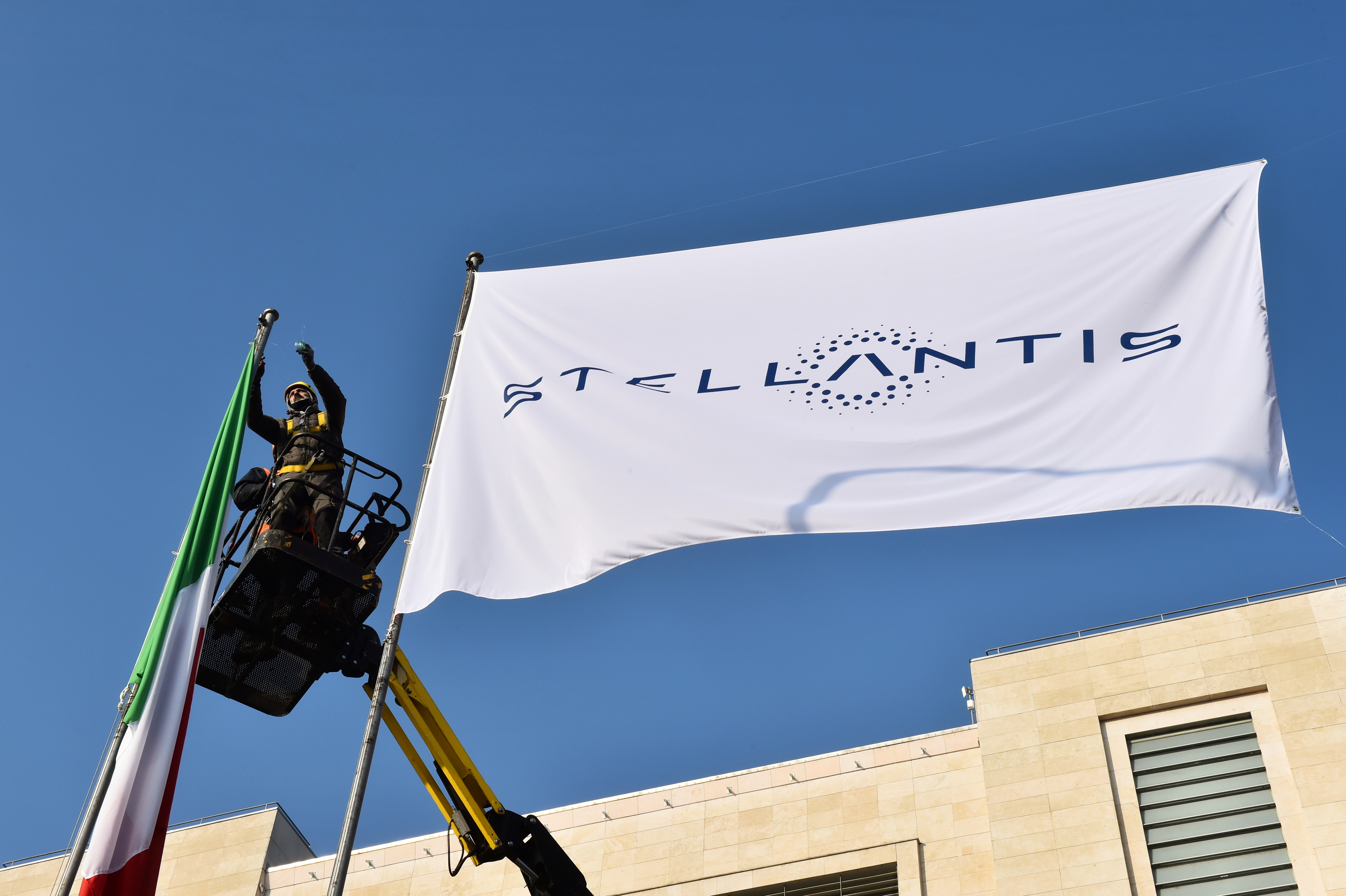 Workers install a flag with the logo of Stellantis, the world's fourth-largest automaker which starts trading in Milan and Paris after Fiat Chrysler and Peugeot maker PSA finalised their merger, at the main entrance of FCA Mirafiori plant in Turin, Italy, January 18, 2021. REUTERS/Massimo Pinca/File Photo