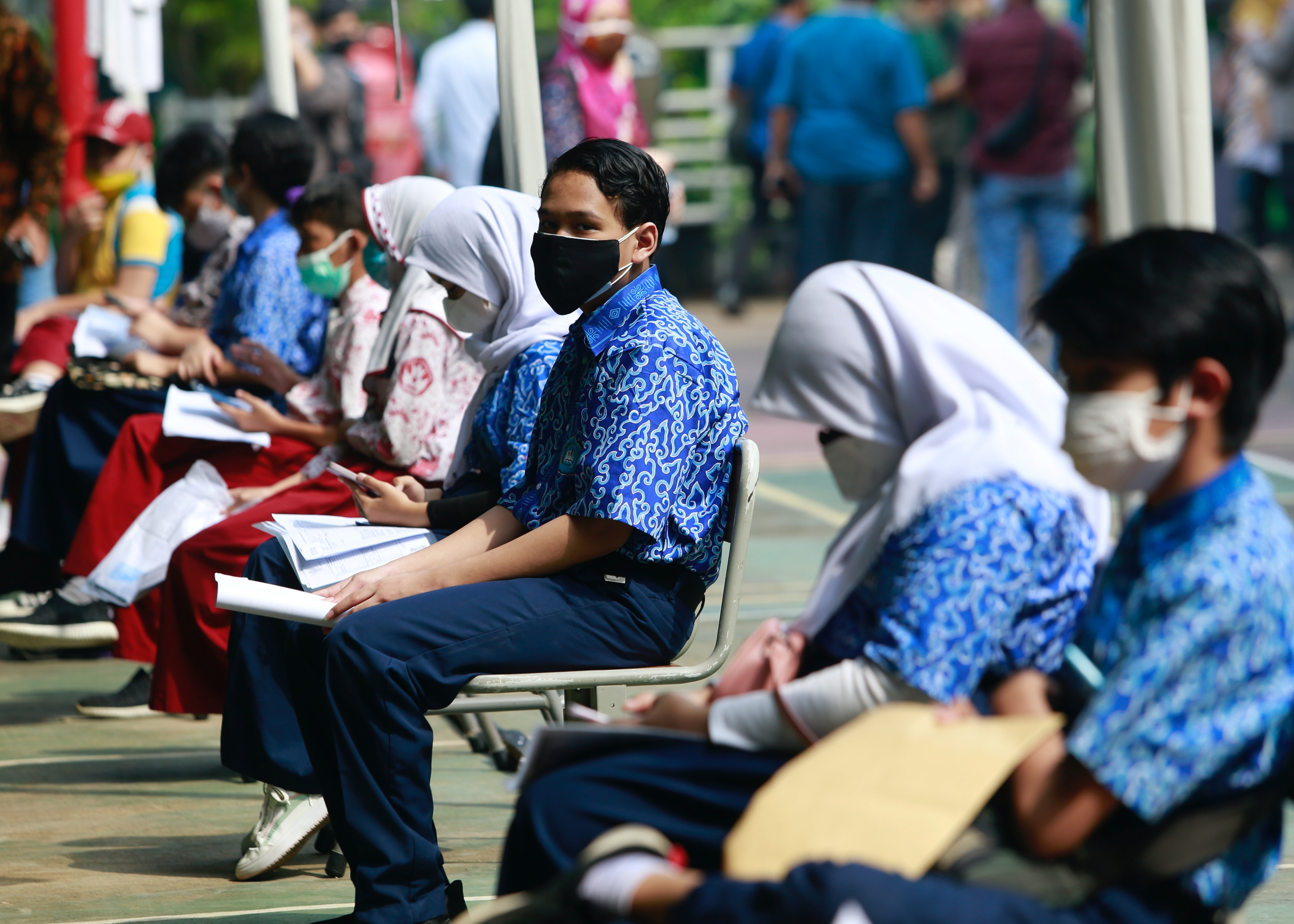 Students wearing protective face masks sit while waiting to receive their dose of the vaccine against the coronavirus disease (COVID-19), during a mass vaccination program for students at a school in Jakarta, Indonesia, July 15, 2021. REUTERS/Ajeng Dinar Ulfiana