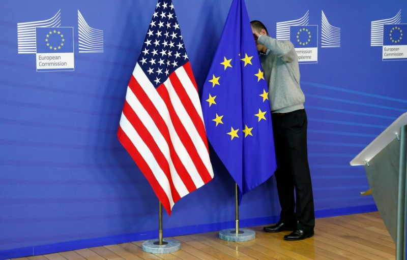 A worker adjusts European Union and U.S. flags at the start of the 2nd round of EU-US trade negotiations for Transatlantic Trade and Investment Partnership at the EU Commission headquarters in Brussels November 11, 2013. REUTERS/Francois Lenoir/File Photo