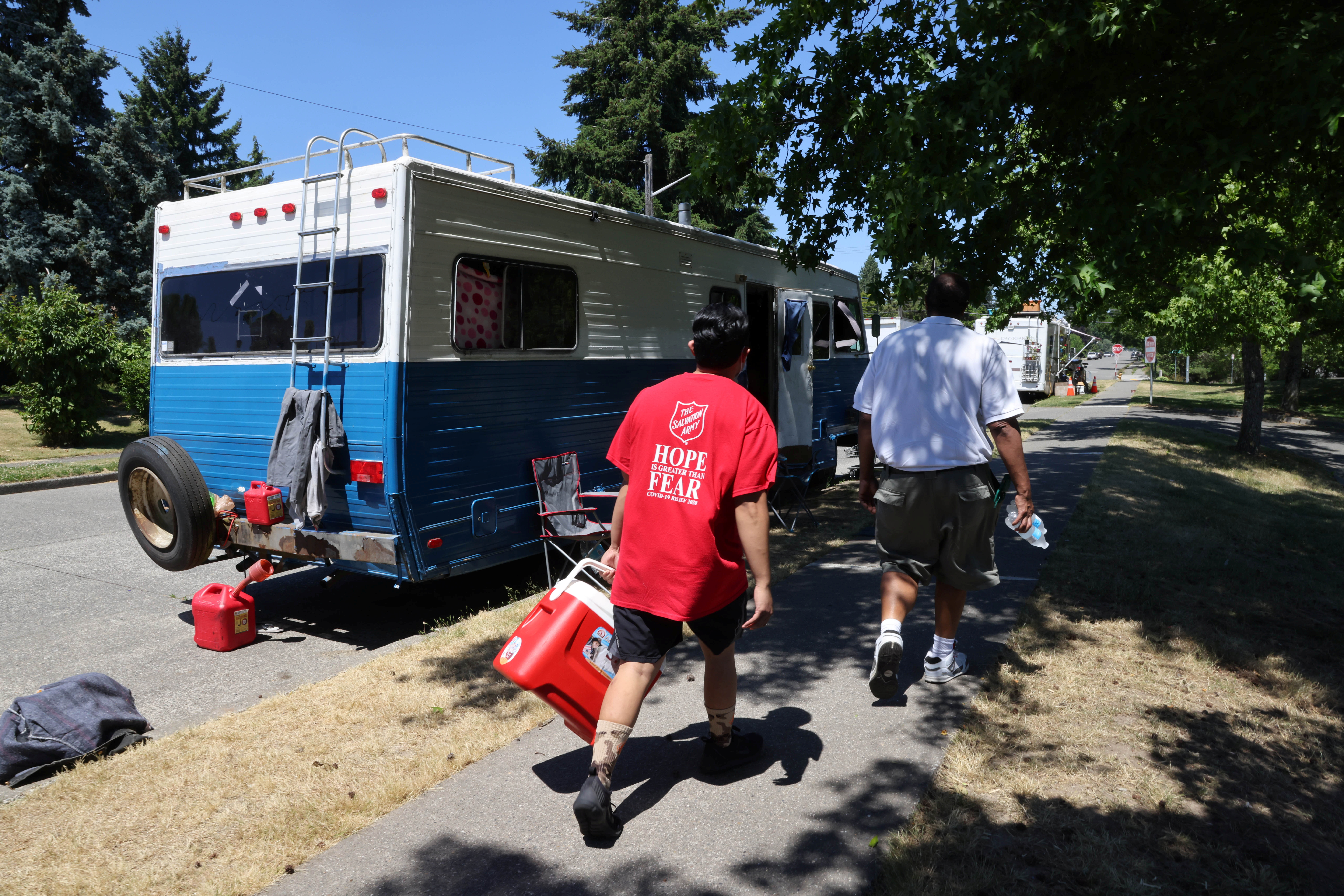 Shanton Alcaraz and Steve Huntley from the Salvation Army Northwest Division hand out water to people who might need it and invite them to their nearby cooling center for food and beverages during a heat wave in Seattle, Washington, U.S., June 27, 2021. REUTERS/Karen Ducey