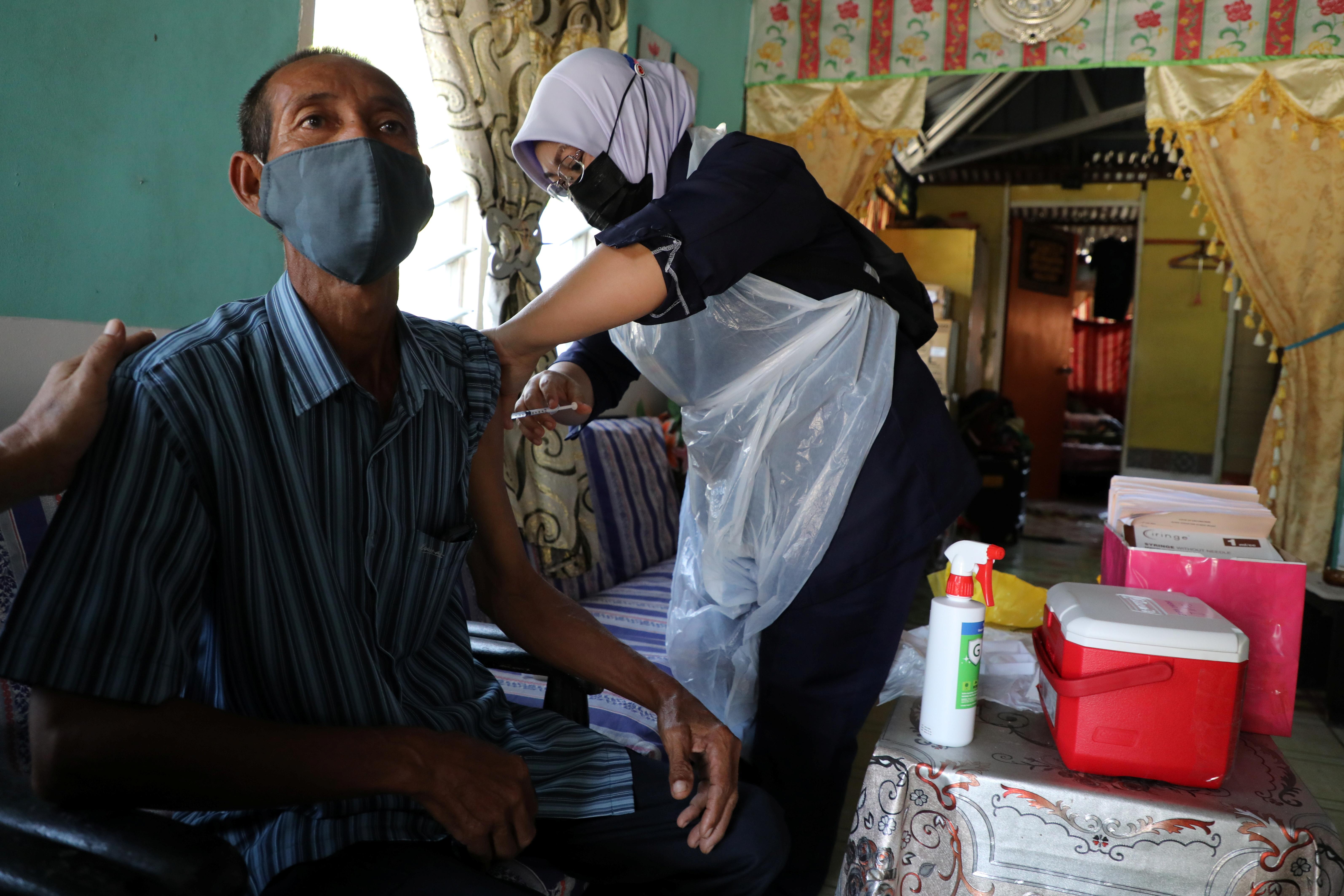 A healthcare worker administers the Sinovac coronavirus disease (COVID-19) vaccine to an elderly man at his home in Sabak Bernam, Malaysia July 1, 2021. REUTERS/Lim Huey Teng