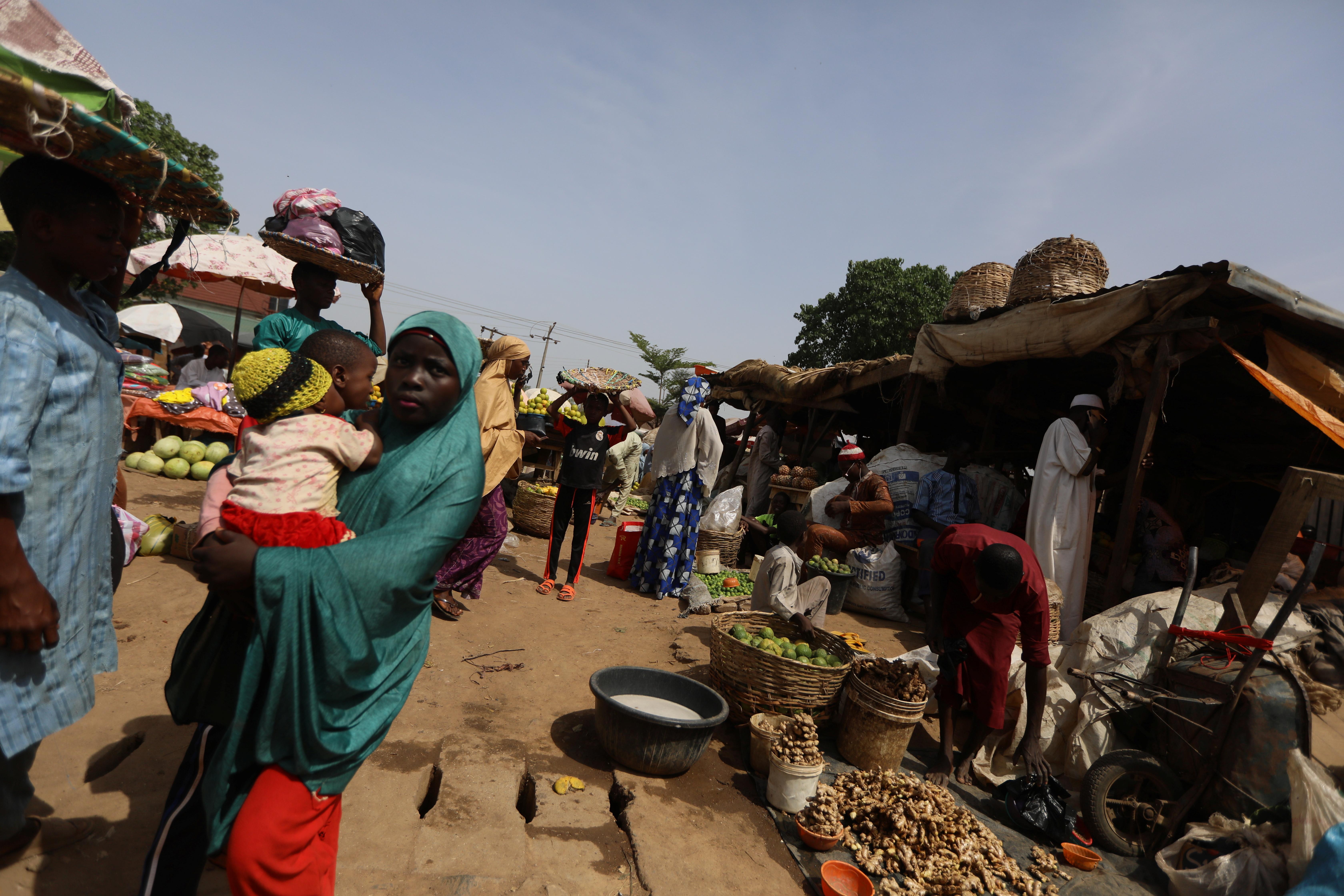 A man puts ginger plant bulbs in buckets at a market in Kaduna, Nigeria. April 30, 2021. REUTERS/Afolabi Sotunde