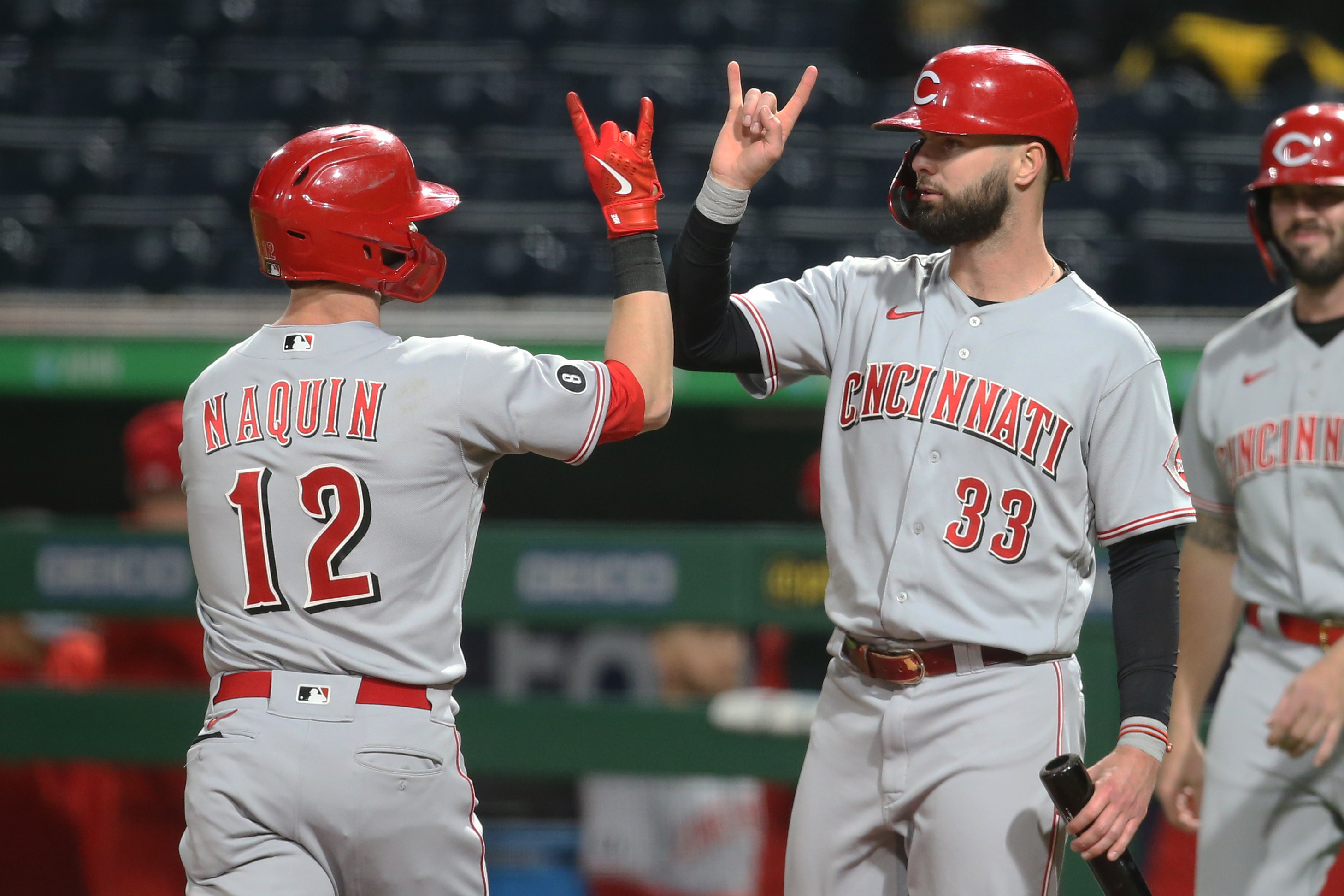 May 10, 2021; Pittsburgh, Pennsylvania, USA; Cincinnati Reds right fielder Jesse Winker (33) congratulates left fielder Tyler Naquin (12) on his three run home run against the Pittsburgh Pirates during the seventh inning at PNC Park. Mandatory Credit: Charles LeClaire-USA TODAY Sports