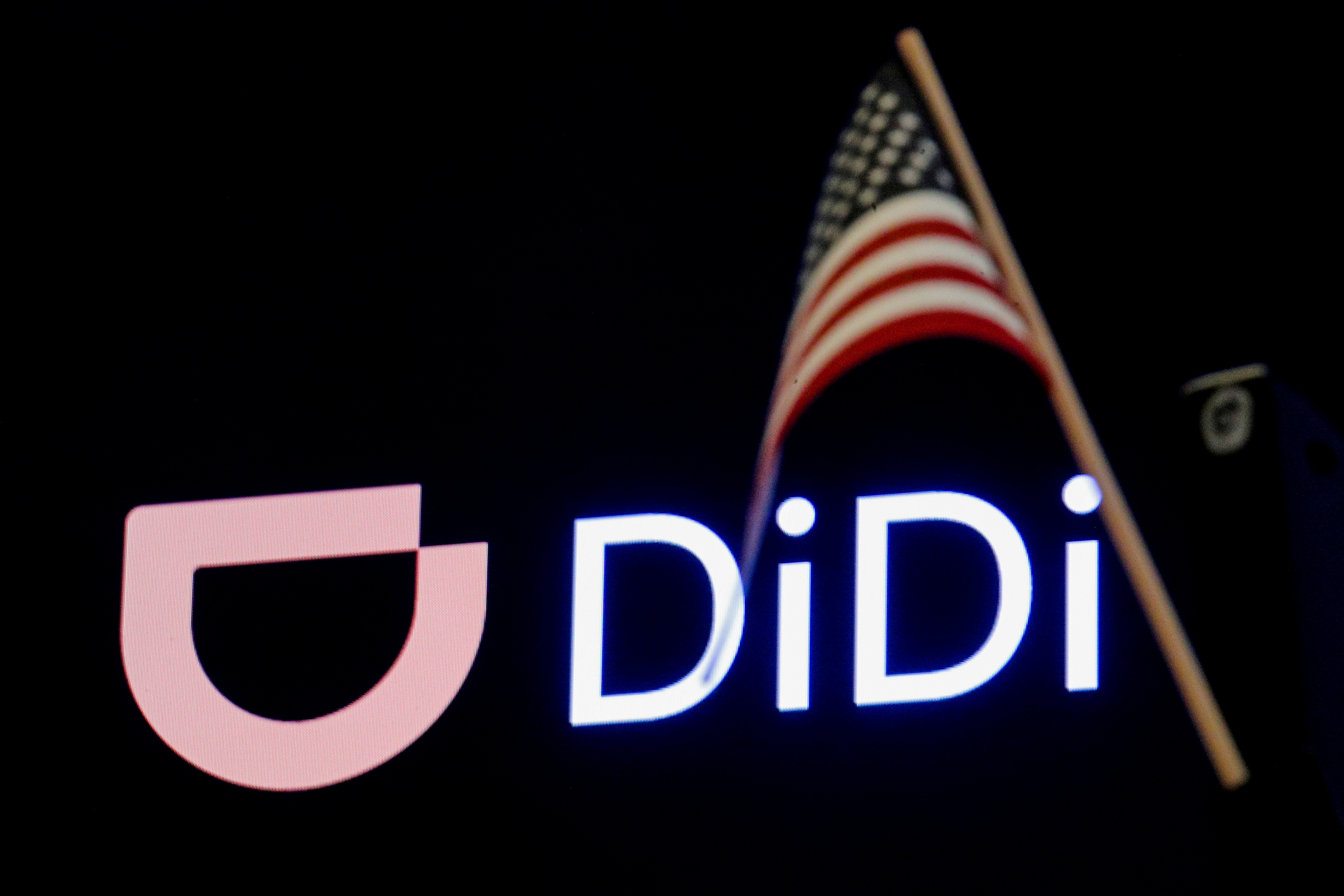 An American flag is seen in front of the logo for Chinese ride hailing company Didi Global Inc. during the IPO on the New York Stock Exchange (NYSE) floor in New York City, U.S., June 30, 2021.  REUTERS/Brendan McDermid/File Photo