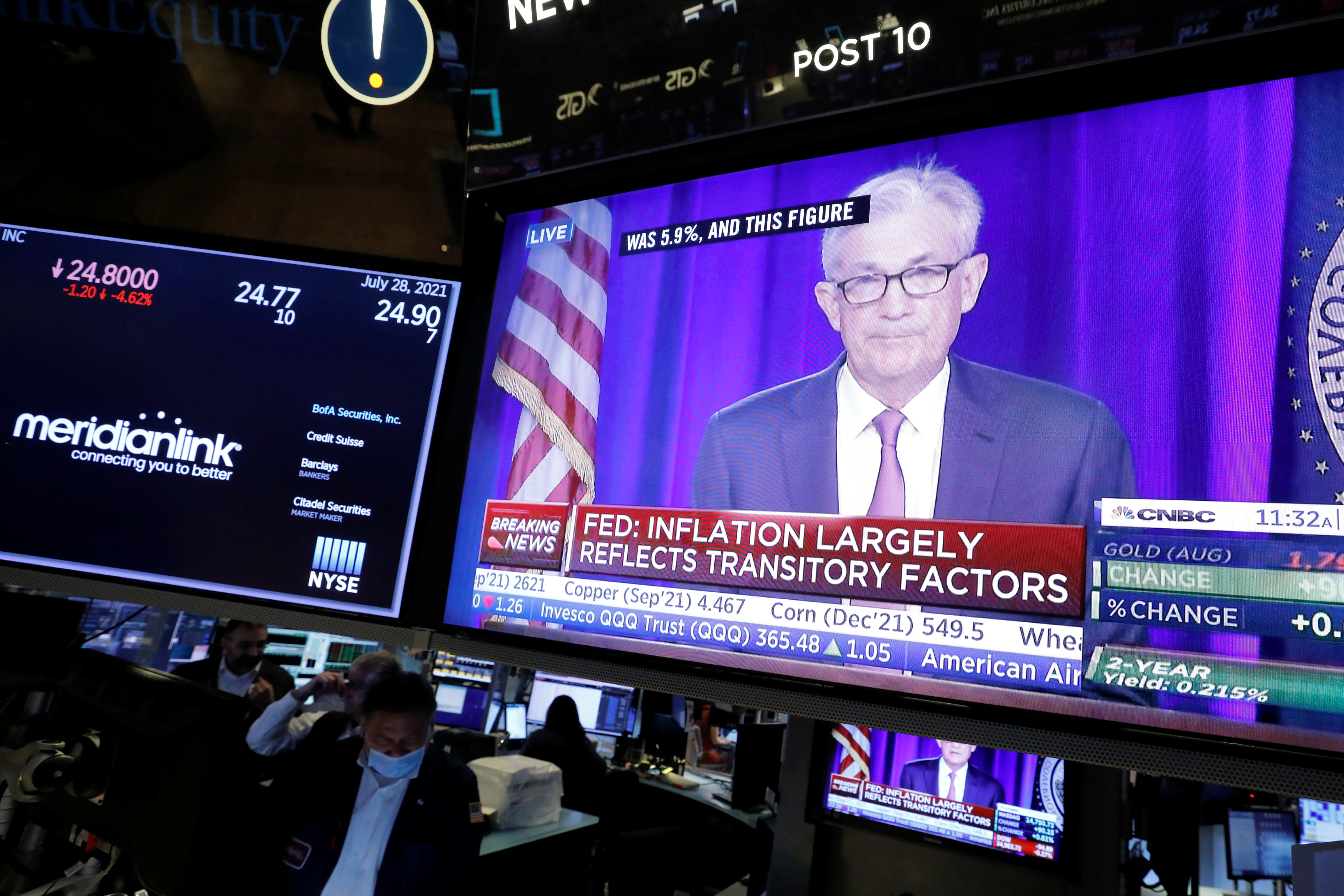 A screen displays a statement by Federal Reserve Chair Jerome Powell following the U.S. Federal Reserve's announcement as traders work on the trading floor at New York Stock Exchange (NYSE) in New York City, New York U.S., July 28, 2021. REUTERS/Andrew Kelly