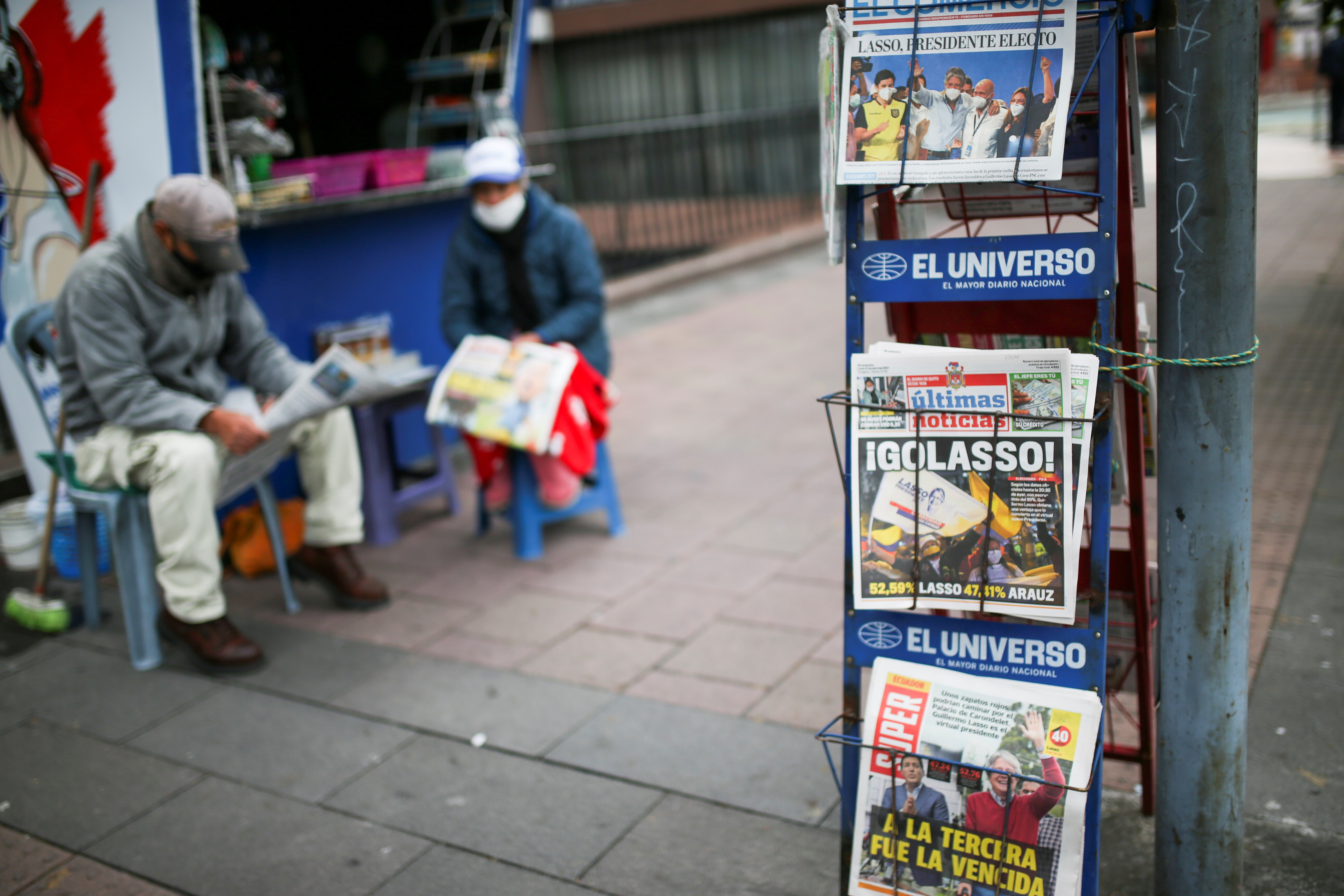 A woman sells newspapers with pictures of presidential candidate Guillermo Lasso, the winner of the presidential election, in Quito, Ecuador April 12, 2021. REUTERS/Luisa Gonzalez