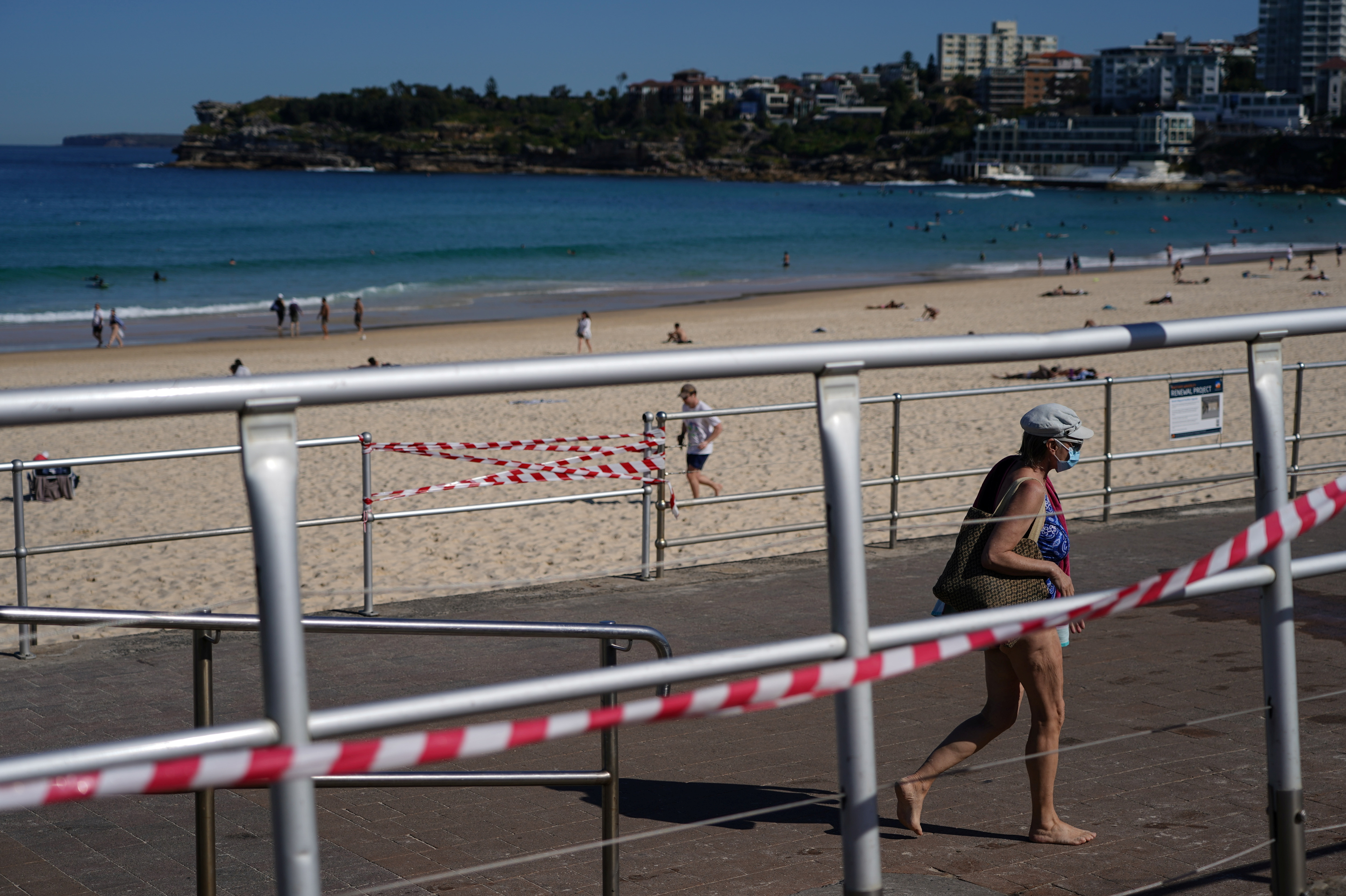 A beachgoer in bathing suit and protective face mask walks up the promenade at Bondi Beach during a lockdown to curb the spread of a coronavirus disease (COVID-19) outbreak in Sydney, Australia, September 1, 2021. REUTERS/Loren Elliott