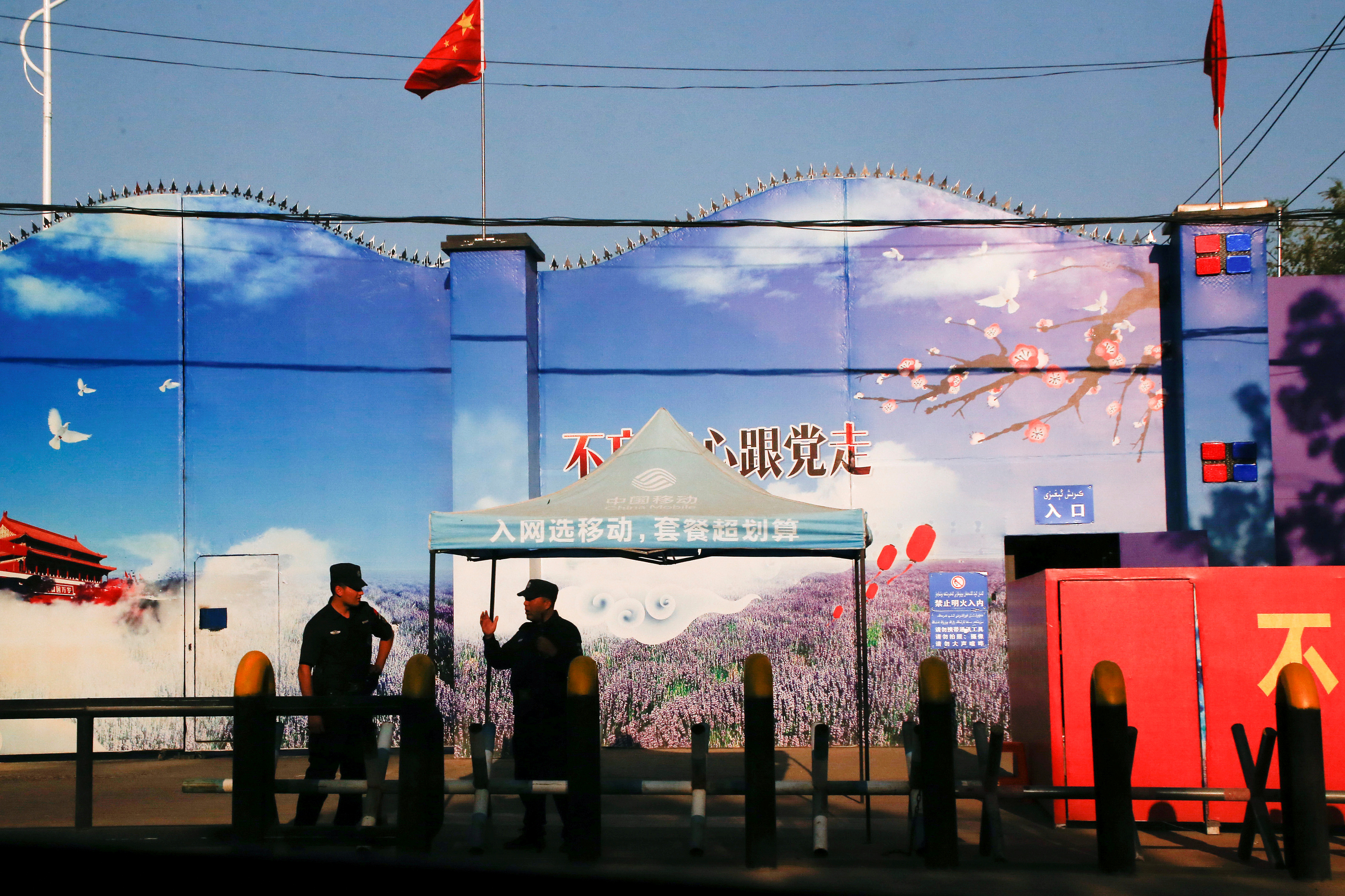 Security guards stand at the gates of what is officially known as a vocational skills education centre in Huocheng County in Xinjiang Uighur Autonomous Region, China September 3, 2018. REUTERS/Thomas Peter/File Photo