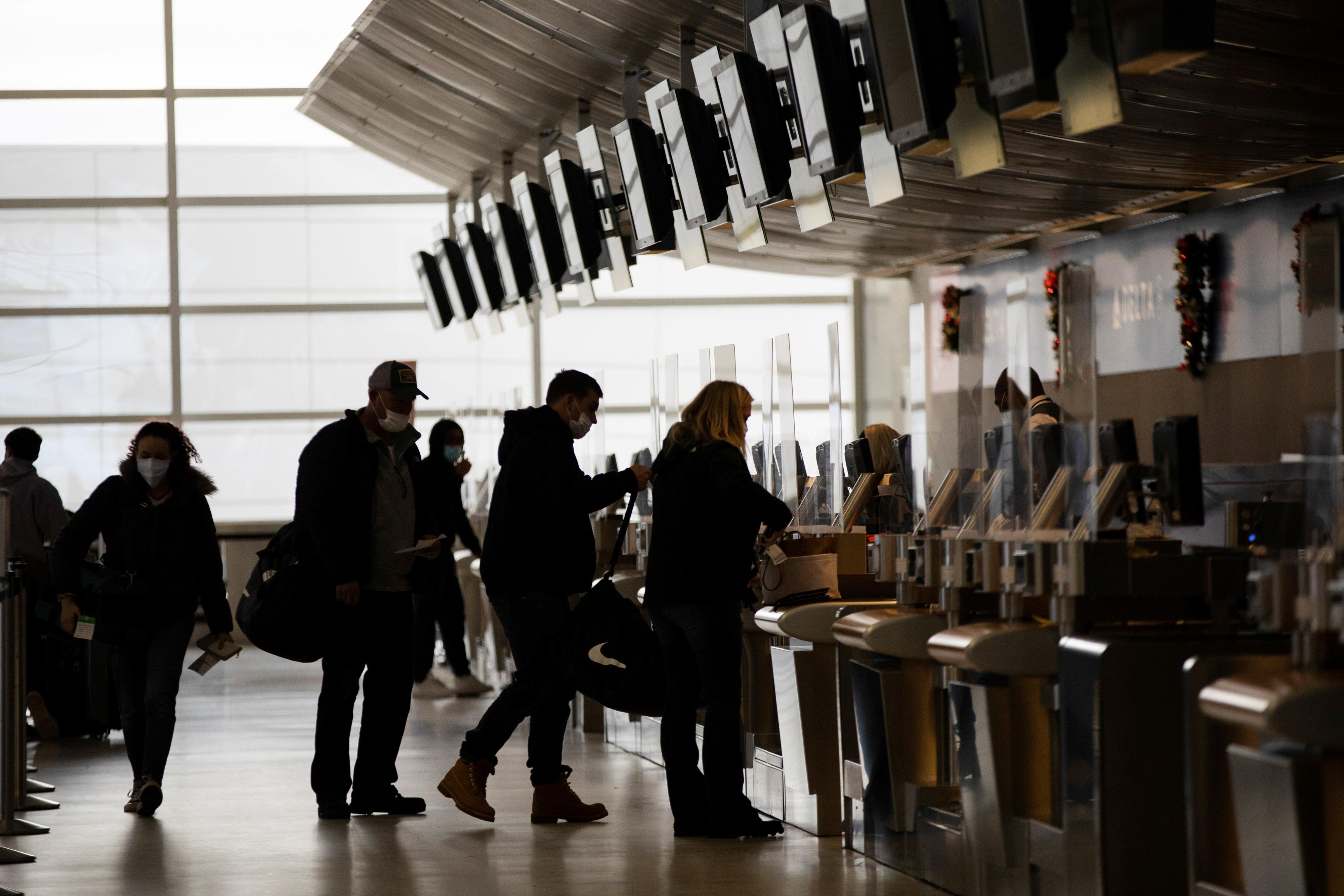 Travelers check in for their flights at Detroit Metropolitan Wayne County Airport, amid the coronavirus disease (COVID-19) pandemic, in Romulus, Michigan, U.S., December 24, 2020. REUTERS/Emily Elconin/File Photo