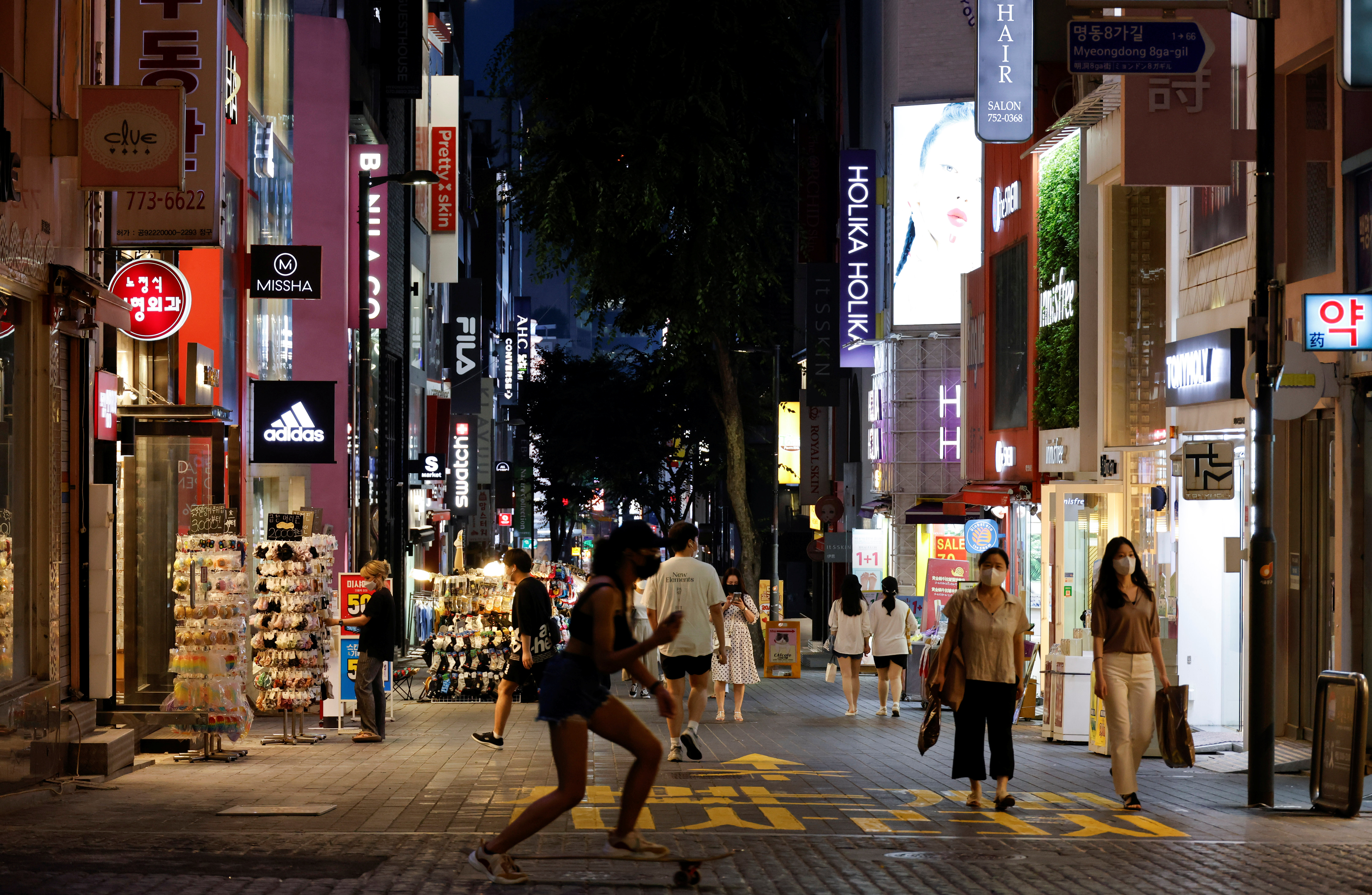 A woman skateboards on a shopping street amid tightened social distancing rules due to the coronavirus disease (COVID-19) pandemic in Seoul, South Korea, July 12, 2021.  REUTERS/Heo Ran