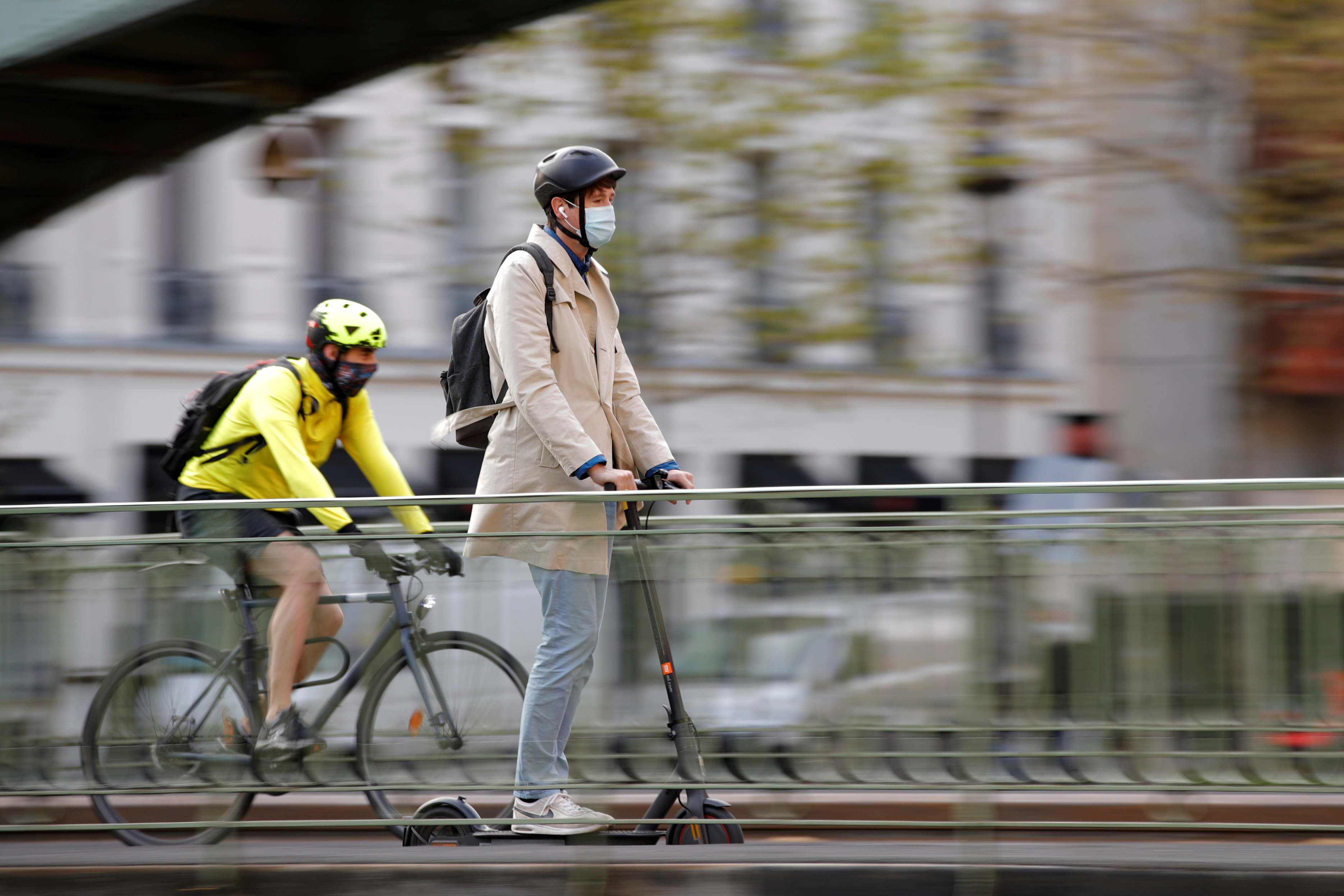 A man, wearing a protective face mask, rides a scooter past a biker on a bridge over the canal Saint-Martin in Paris amid the coronavirus (COVID-19) outbreak in France, April 22, 2021. REUTERS/Sarah Meyssonnier