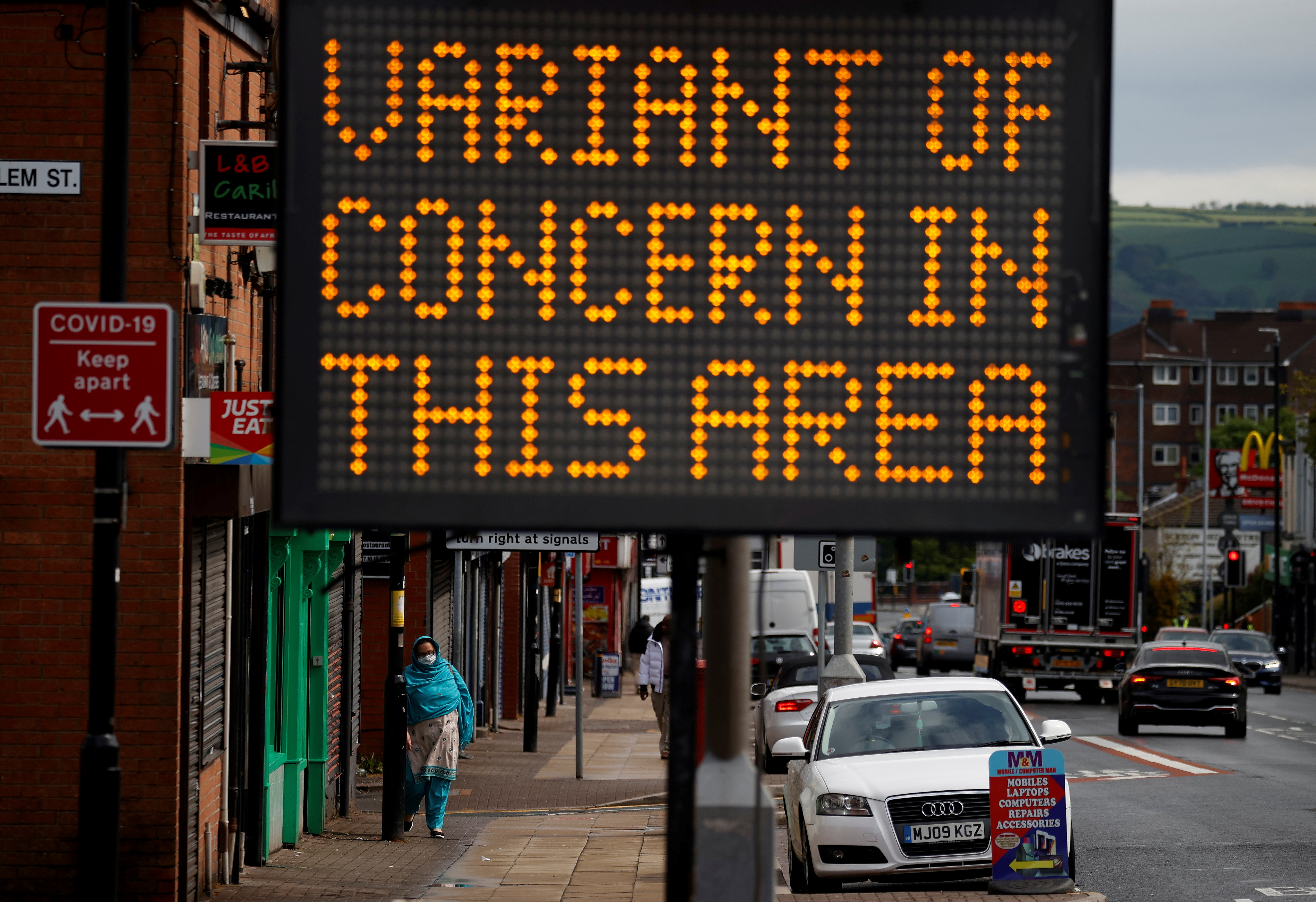 A woman walks past an information sign amid the outbreak of the coronavirus disease (COVID-19) in Bolton, Britain, May 17, 2021. REUTERS/Phil Noble/File Photo