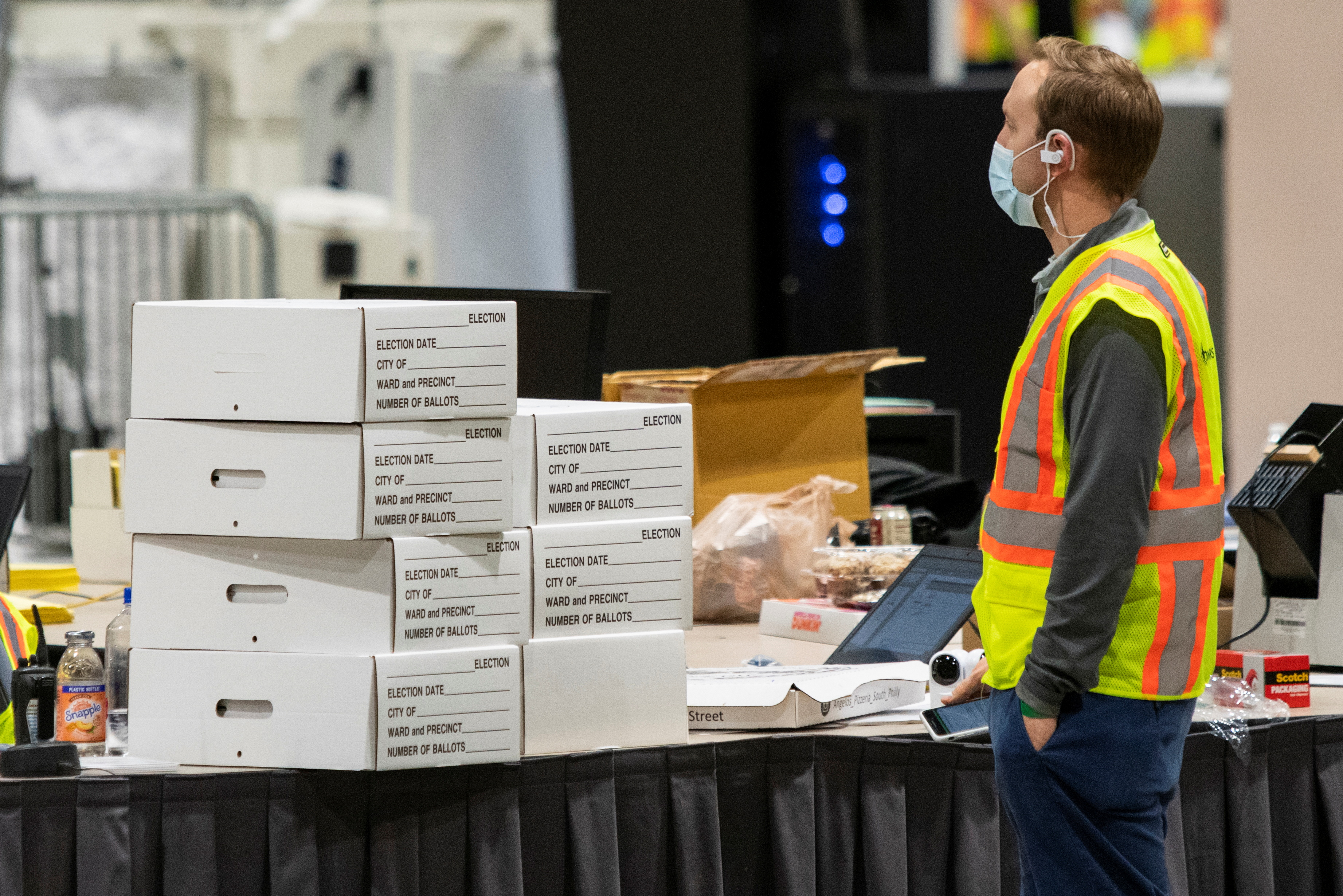An electoral worker stands next to boxes with ballot material following the 2020 U.S. presidential election, in Philadelphia, Pennsylvania, U.S. November 6, 2020. REUTERS/Eduardo Mu?oz