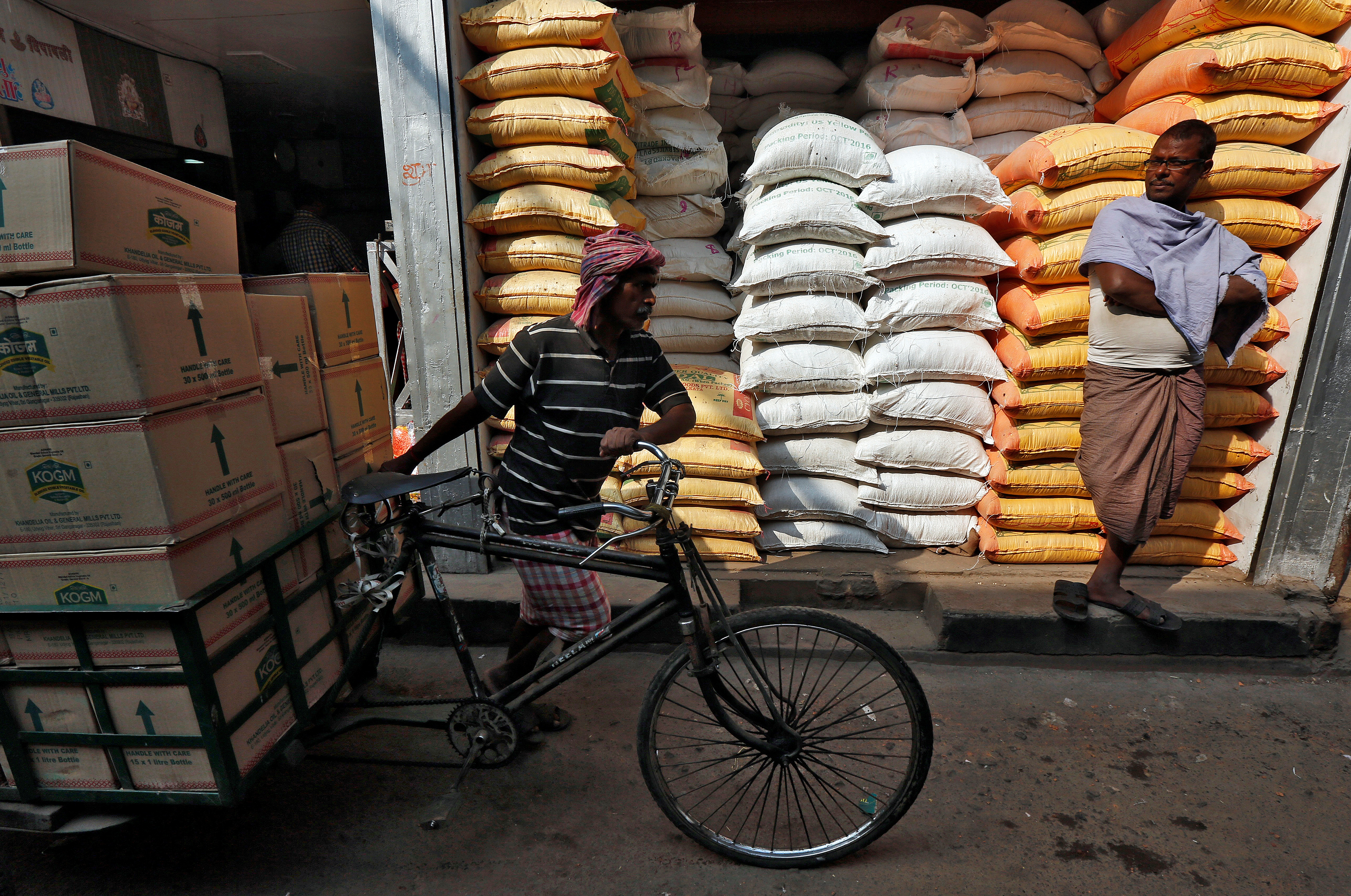 A labourer carries vegetable oil packets on a tricycle as a man stands in front of his shop selling food grains, at a wholesale market in Kolkata, India, January 4, 2017.  REUTERS/Rupak De Chowdhuri